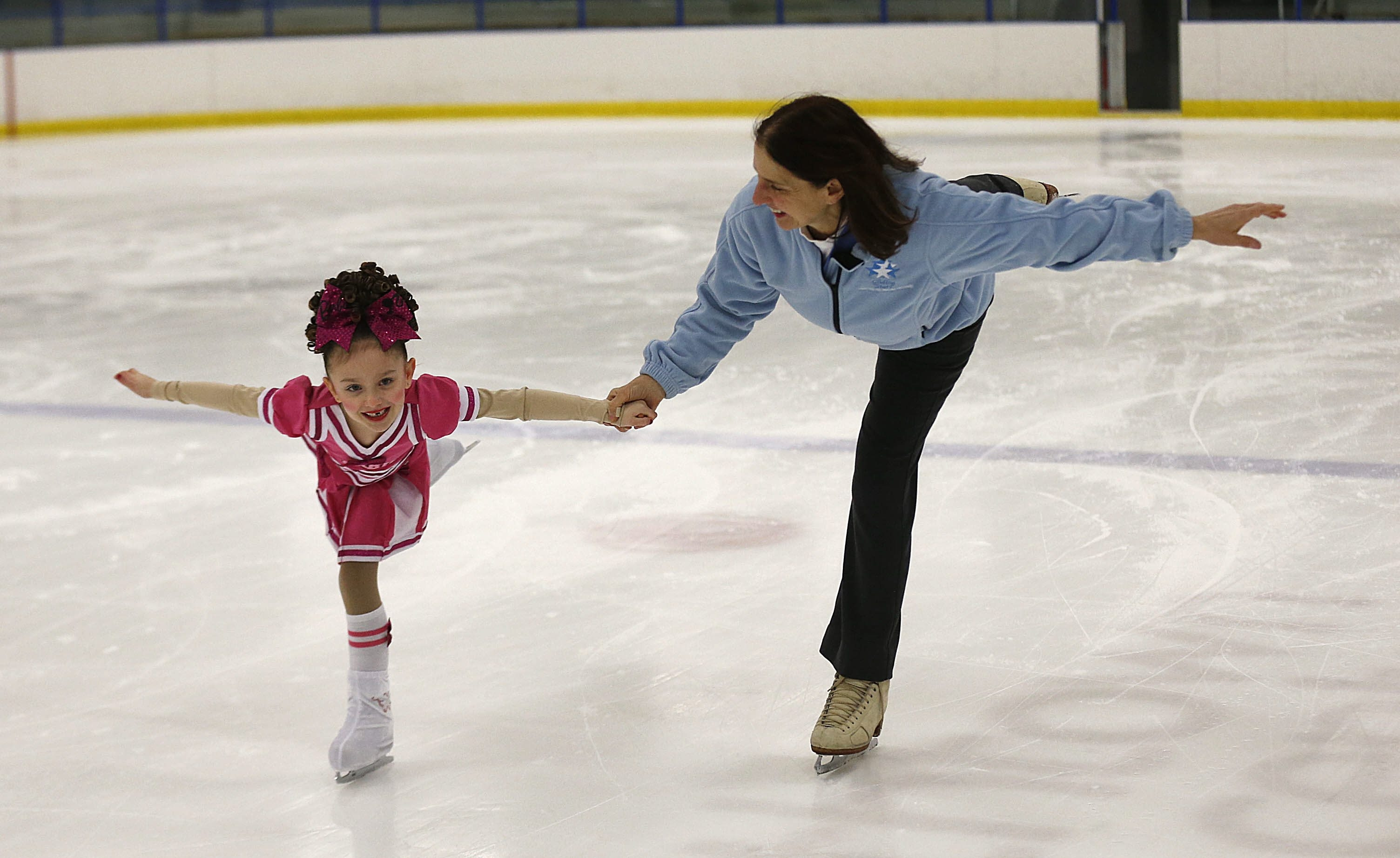 Elizabeth O'Donnell works with Riley Vaccaro, 6, for upcoming performance of Gliding Stars. They were on the rink at the Northtown Center in Amherst.