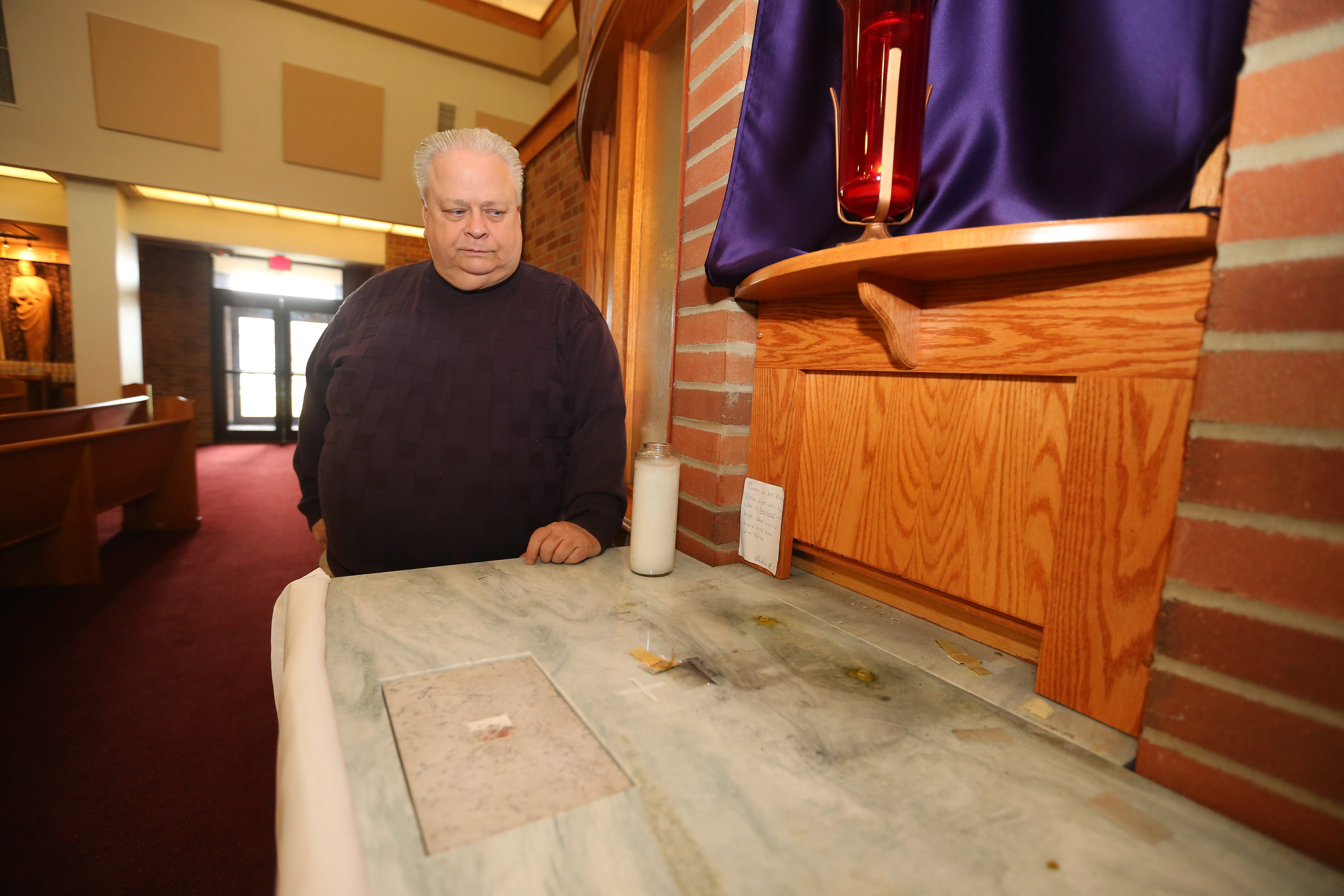 Rev. James Judge, pastor of St. Martin of Tours Catholic Church on Abbott Road, looks at empty spot on altar for tabernacle, which holds sacred hosts. It was stolen at about 1 p.m. Wednesday.