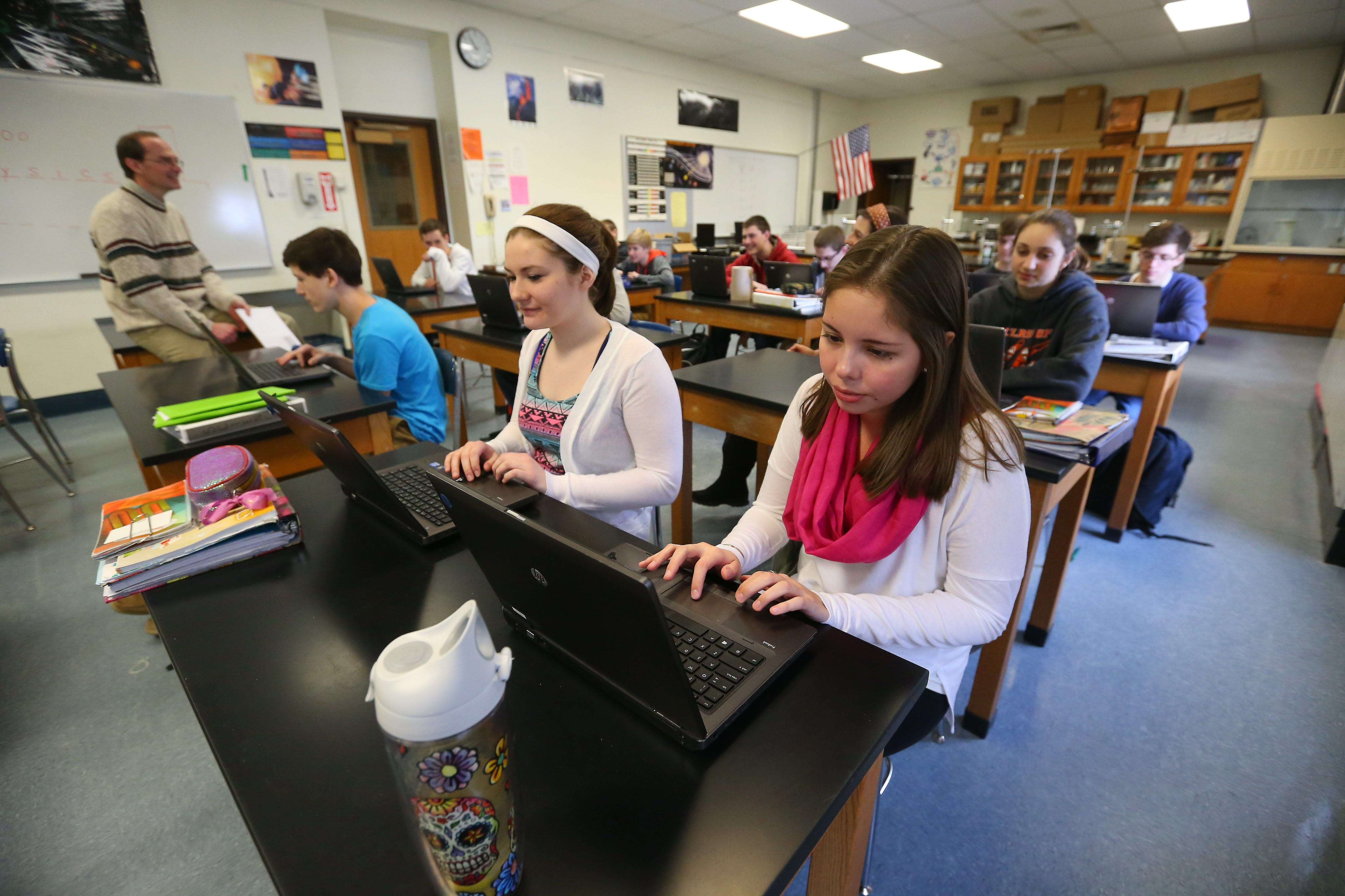 Maddy Caya, left, and Kamryn Hartranft work on a project during a computer coding class at Akron High School. Behind them is Carly Staebell.