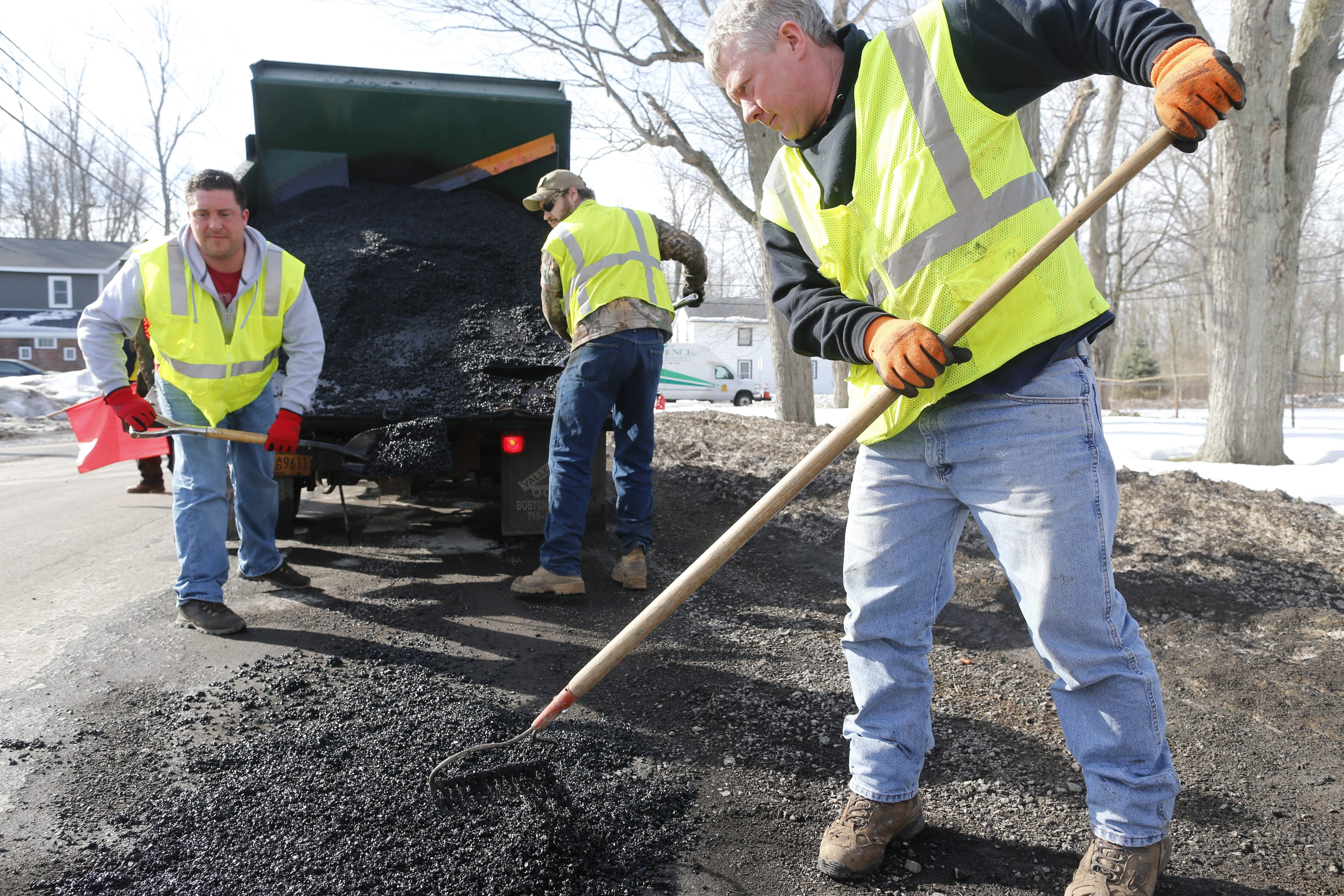 From left, Robert Rine, Scott Boyer and Sean Kelly of the Erie County Public Works Department use cold patch to fill potholes on Goodrich Road in Clarence on Friday.