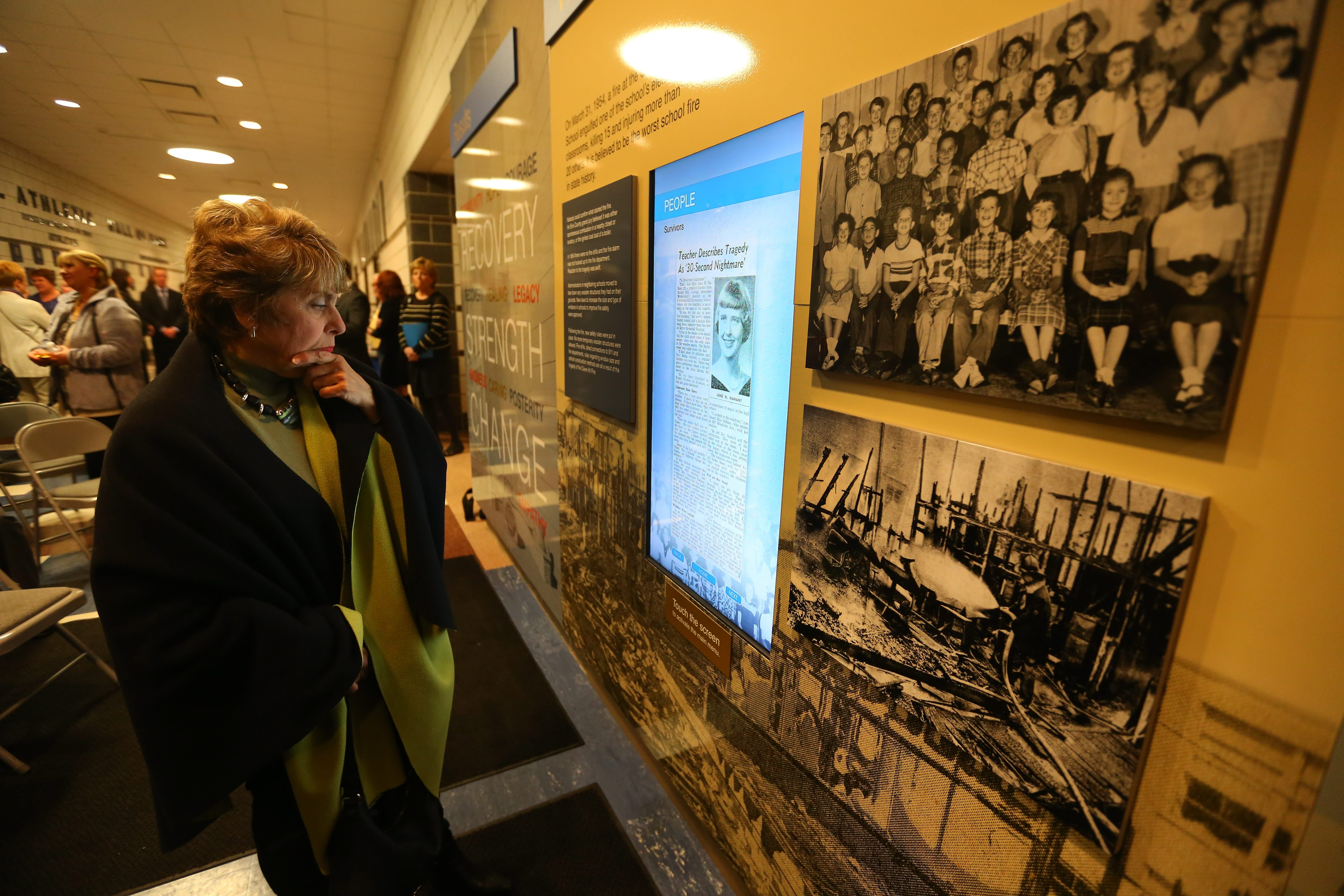 Mark Mulville/Buffalo News Mary Margaret Romano-Helenbrook looks over an interactive video Wednesday on the wall display recounting the 1954 fire at Cleveland Hill Elementary School that killed 15 students March 31, 1954. A member of the high school Class of 1960, she had just left the music classroom before the explosion and fire occcurred.