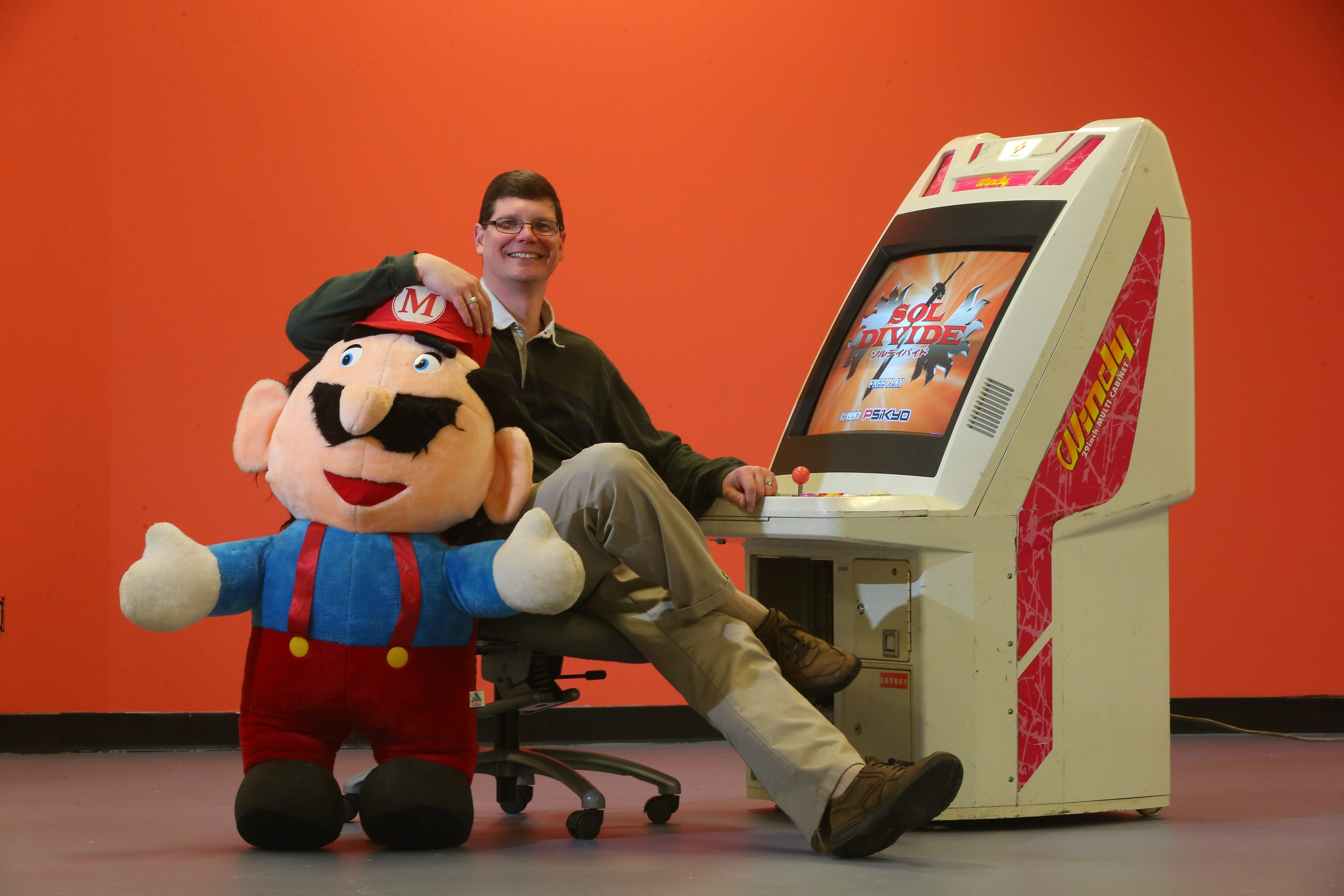 Michael Thomasson, with an old Japanese video game and a stuffed Mario is a Canisius College professor of  animation and video game design. He has been certified by the Guinness World Records Gamer's Edition as owning the world's largest video game collection with more than 10,500 games.
