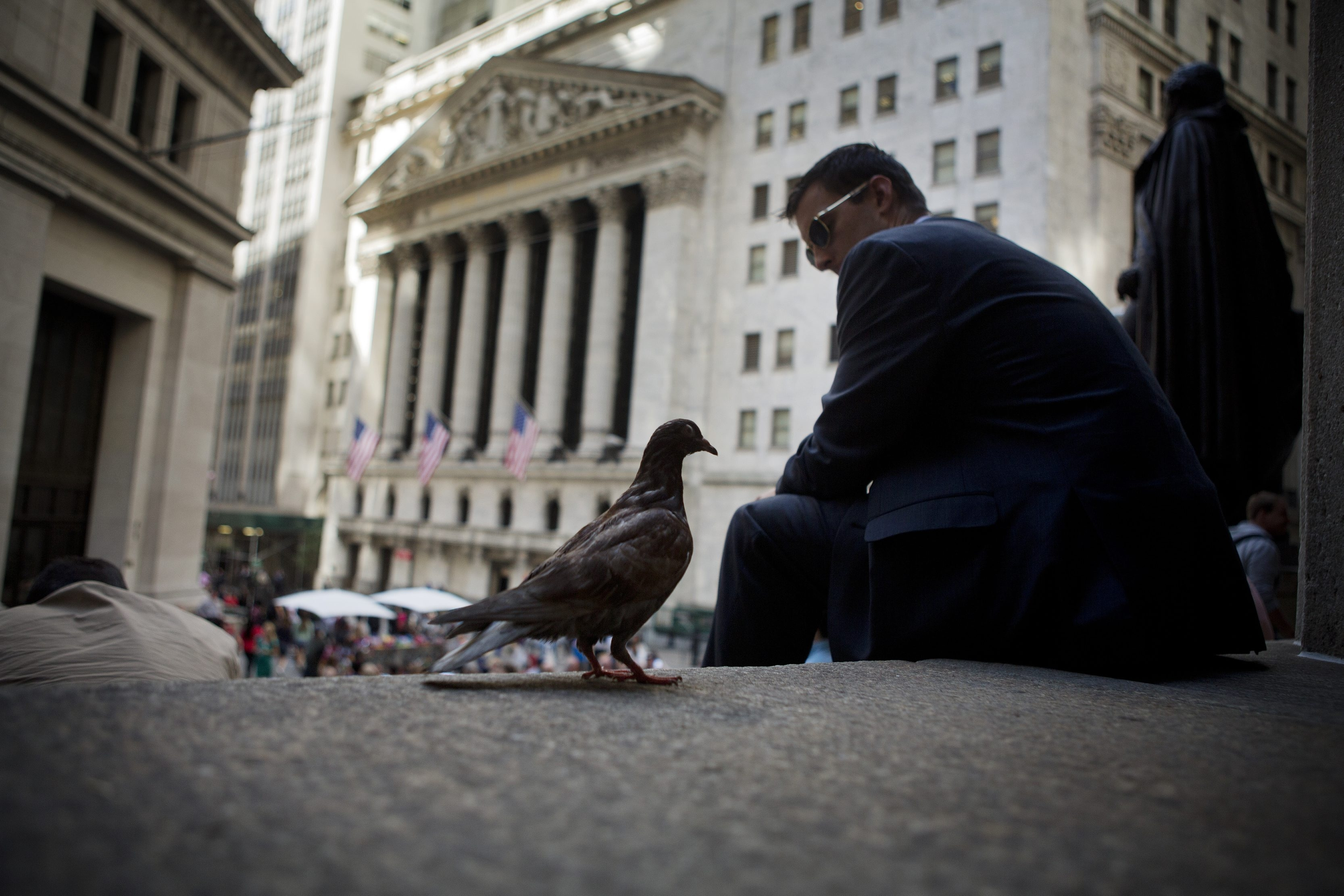 On the Federal Hall steps, a pigeon keeps a man company across from the New York Stock Exchange in climate of buybacks, which are helping to prop up a bull market that is entering its seventh year just as investors bail out and head back to bonds.