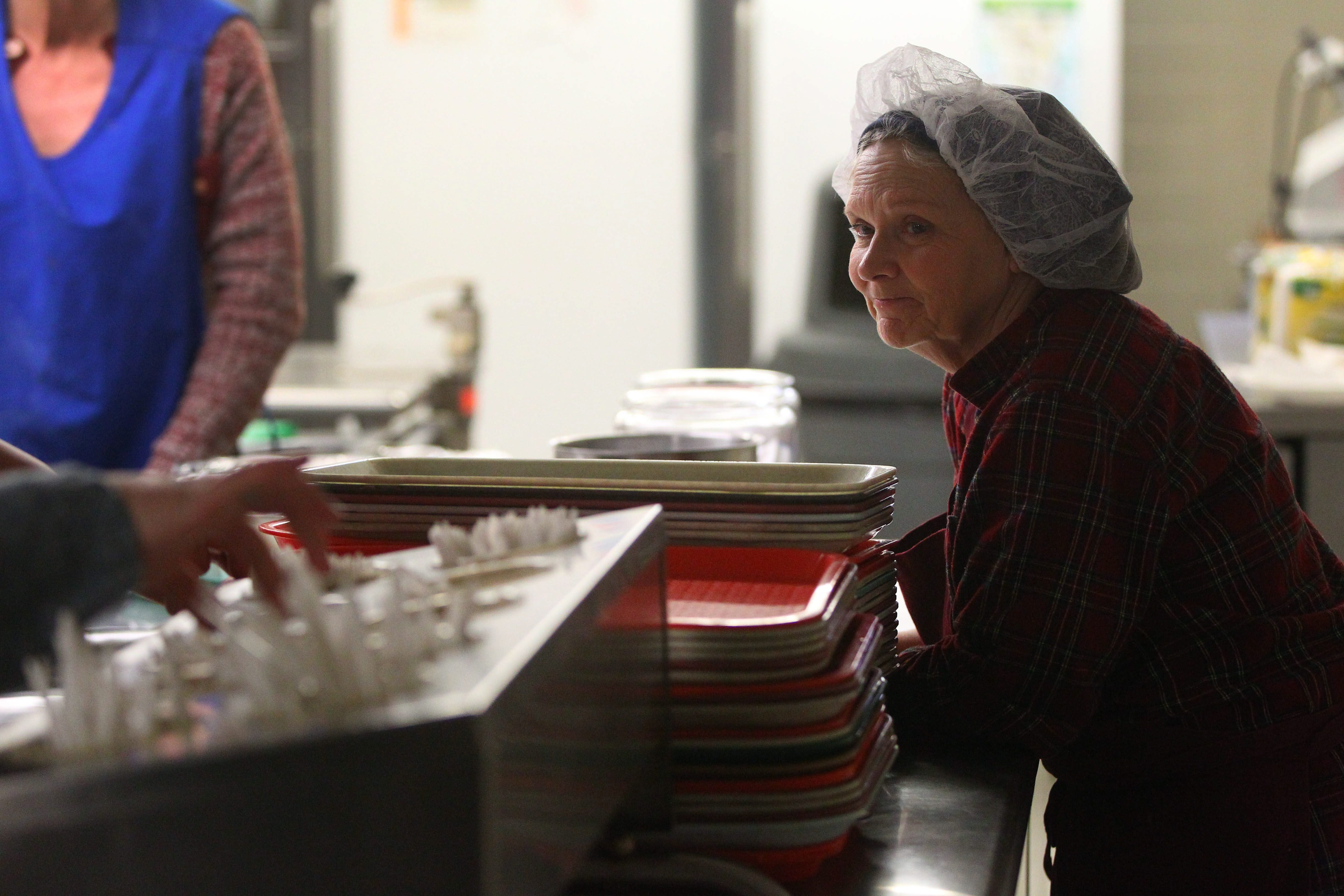 Bonnie McCarthy from the Welfare to Work program helps distribute food trays at the Community Missions on Buffalo Avenue in Niagara Falls. Niagara County Coalition for Services to the Homeless will hold a Poverty Conference on Friday at Niagara U.