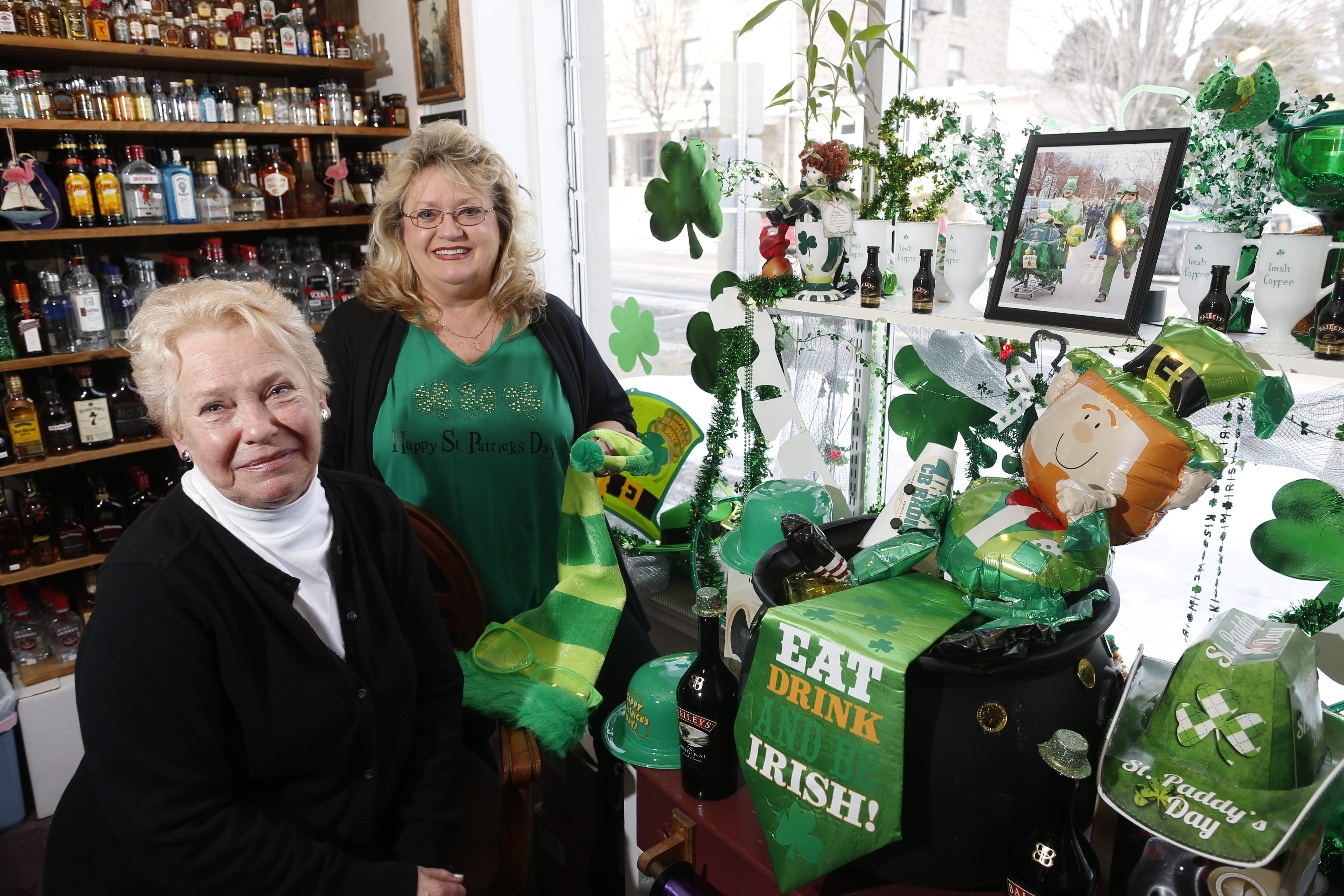 Dotty Riordan, left, and Cheryl Irish-Butera, president of the Youngstown Business Association, pose in front of a St. Patrick's Day display at Anchor Spirits in Youngstown.