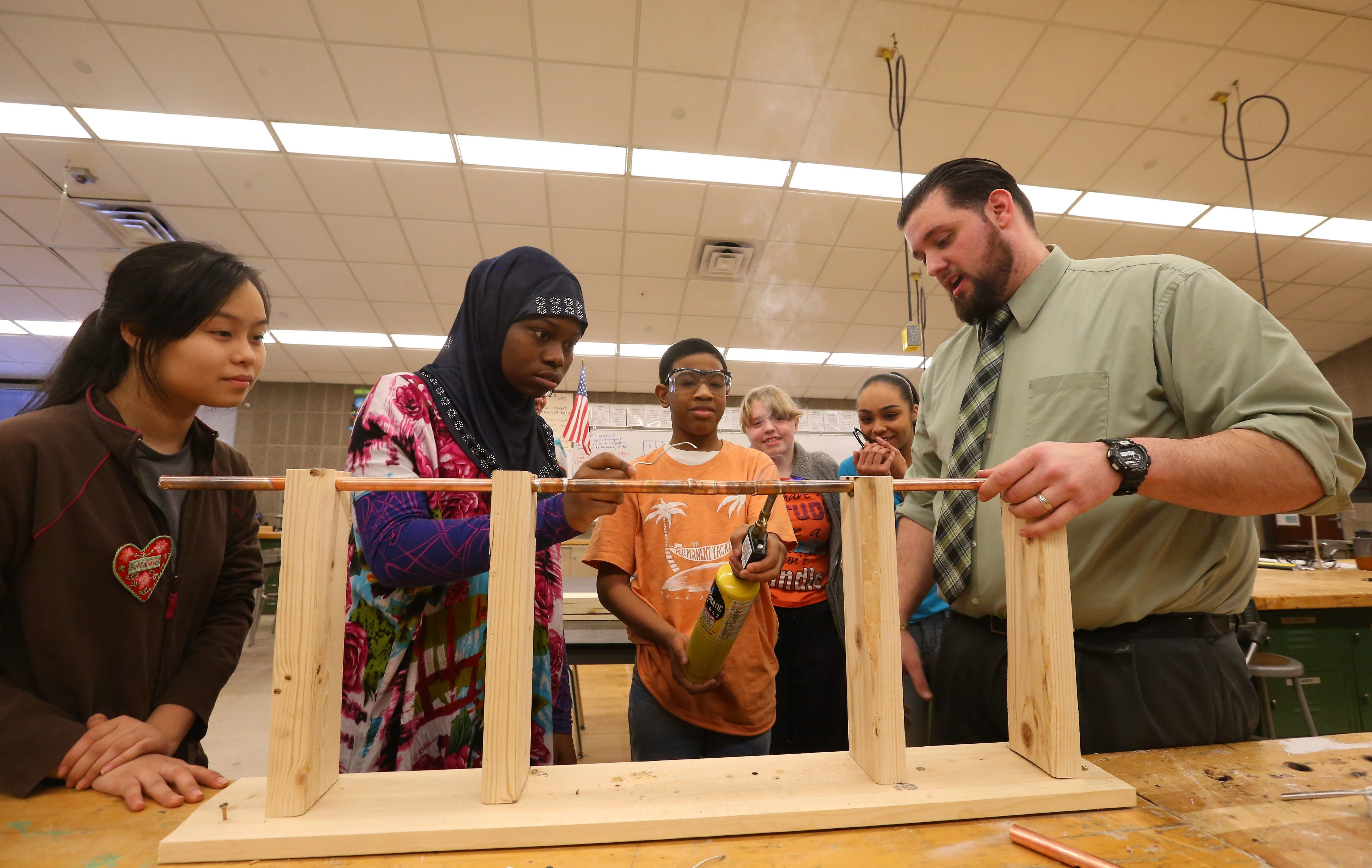 Christopher Traugott teaches students Maryan Abdi, Delano Donell, Patricia Hill and Ariana Cortes how to fix a burst pipe at Waterfront Elementary School Tuesday.