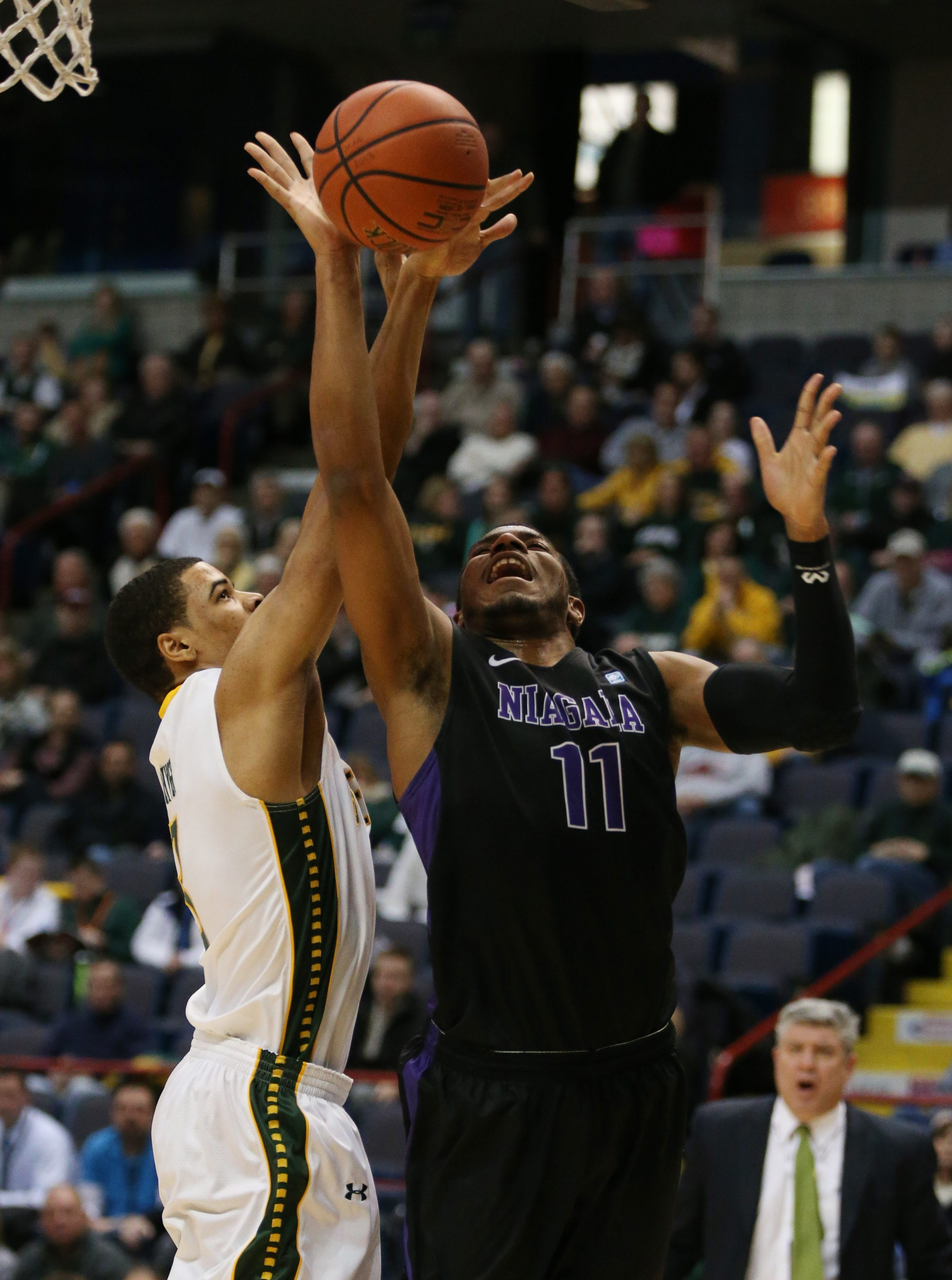 Niagara Purple Eagles forward Ramone Snowden (11) has his shot blocked by Siena Saints guard Ryan Oliver (3) in the first half during the MAAC Championship tournament at Time Union Center in Albany,NY on Thursday, March 5, 2015.  (James P. McCoy/ Buffalo News)