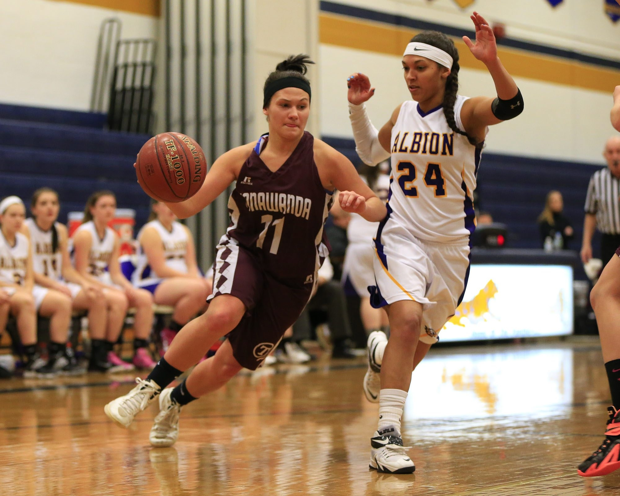 Tonawanda's Savanna Allen drives to the basket as she is defended by Albion's Justice Nauden during action at Sweet Home High School.