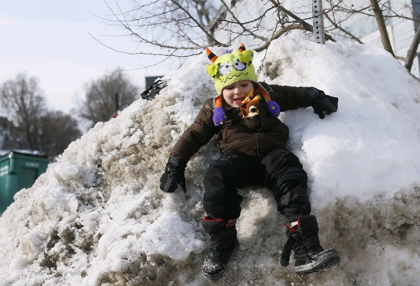 Snow piles like this one scaled last Friday by 4-year-old Rowan Finnerty on Plymouth Avenue will start slowly dwindling this week with temperatures in the 40s. (Derek Gee/Buffalo News)