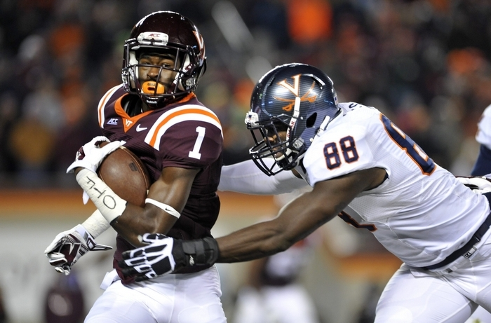 Virginia linebacker and edge rusher Max Valles, tackling Virginia Tech's Isaiah Ford, is the youngest player in the draft at age 20. (Getty Images)