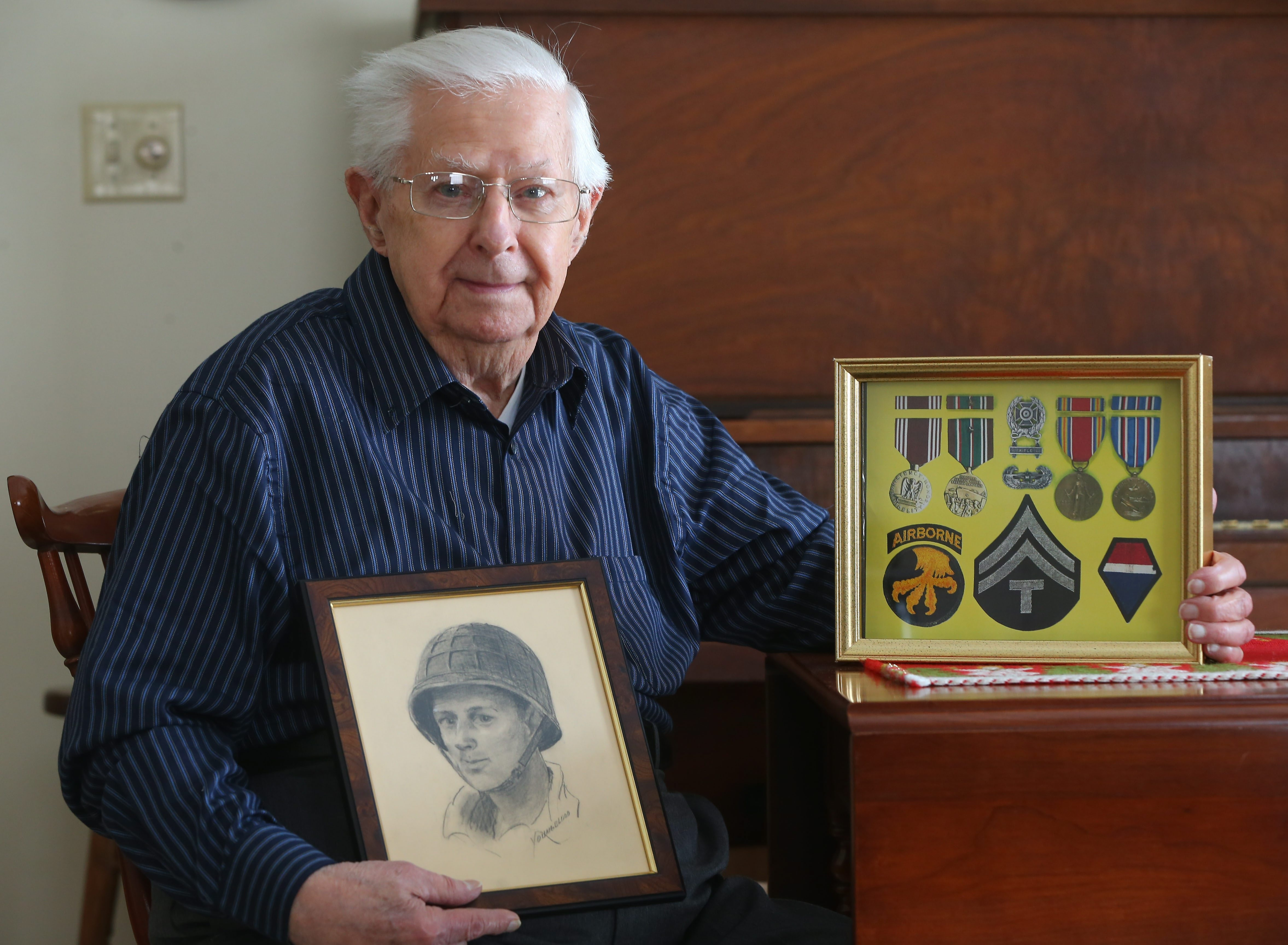 Dick Matthies, with medals and insignia, along with a sketch of himself, recalls how his unit had inflatable tanks, artillery, vehicles and even fake troops to fool the enemy.