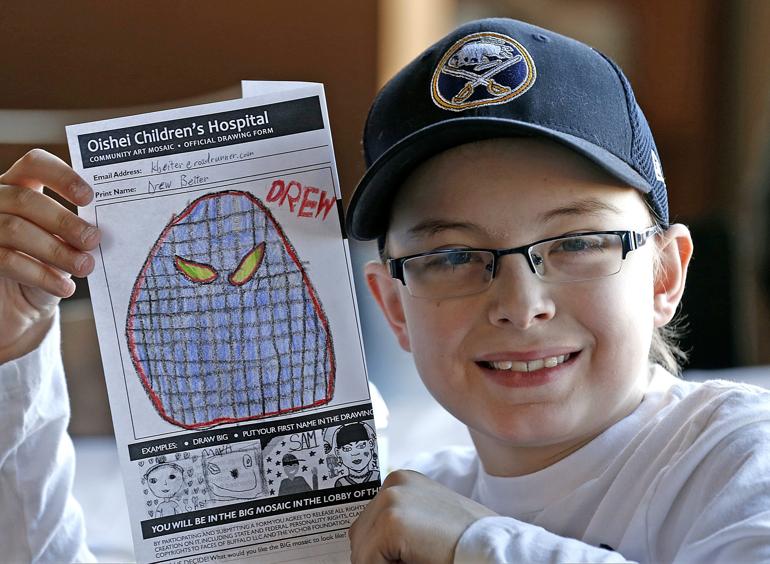 Drew Beiter, 9, of Lockport, displays his drawing of a lacrosse player's face, which will be included in the hospital mosaic. Drew suffers from acute lymphoblastic leukemia.