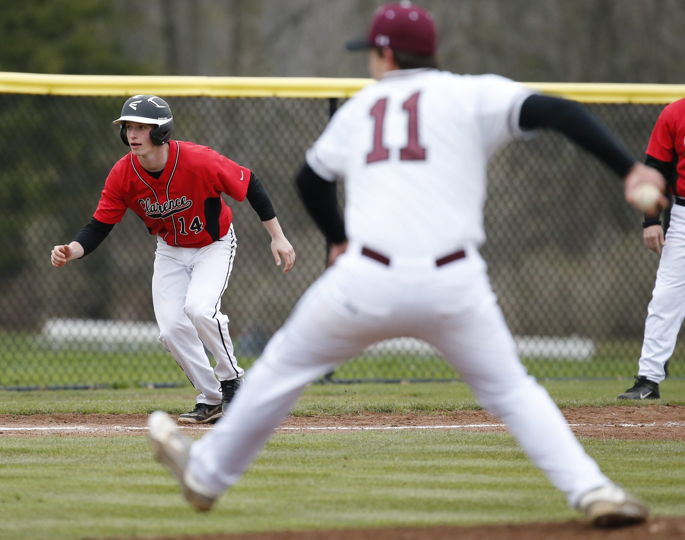 Zach Randall of Clarence leads off third base in the first inning at Orchard Park on Monday. The host Quakers won, 9-4, to remain undefeated.