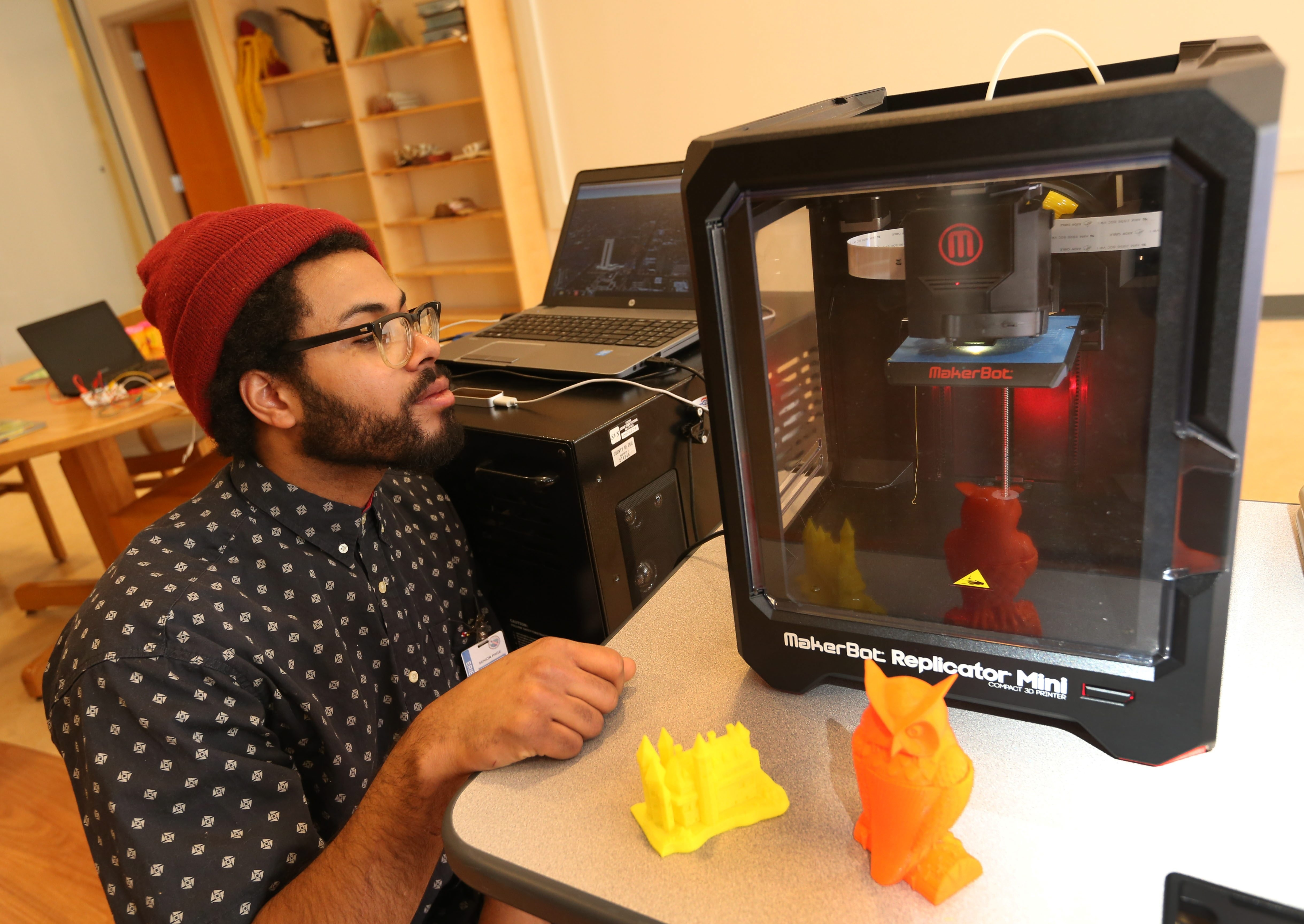 """Trevor Brown demonstrates the 3-D printer available for use at the Central Library in a new space called the """"Launch Pad."""""""