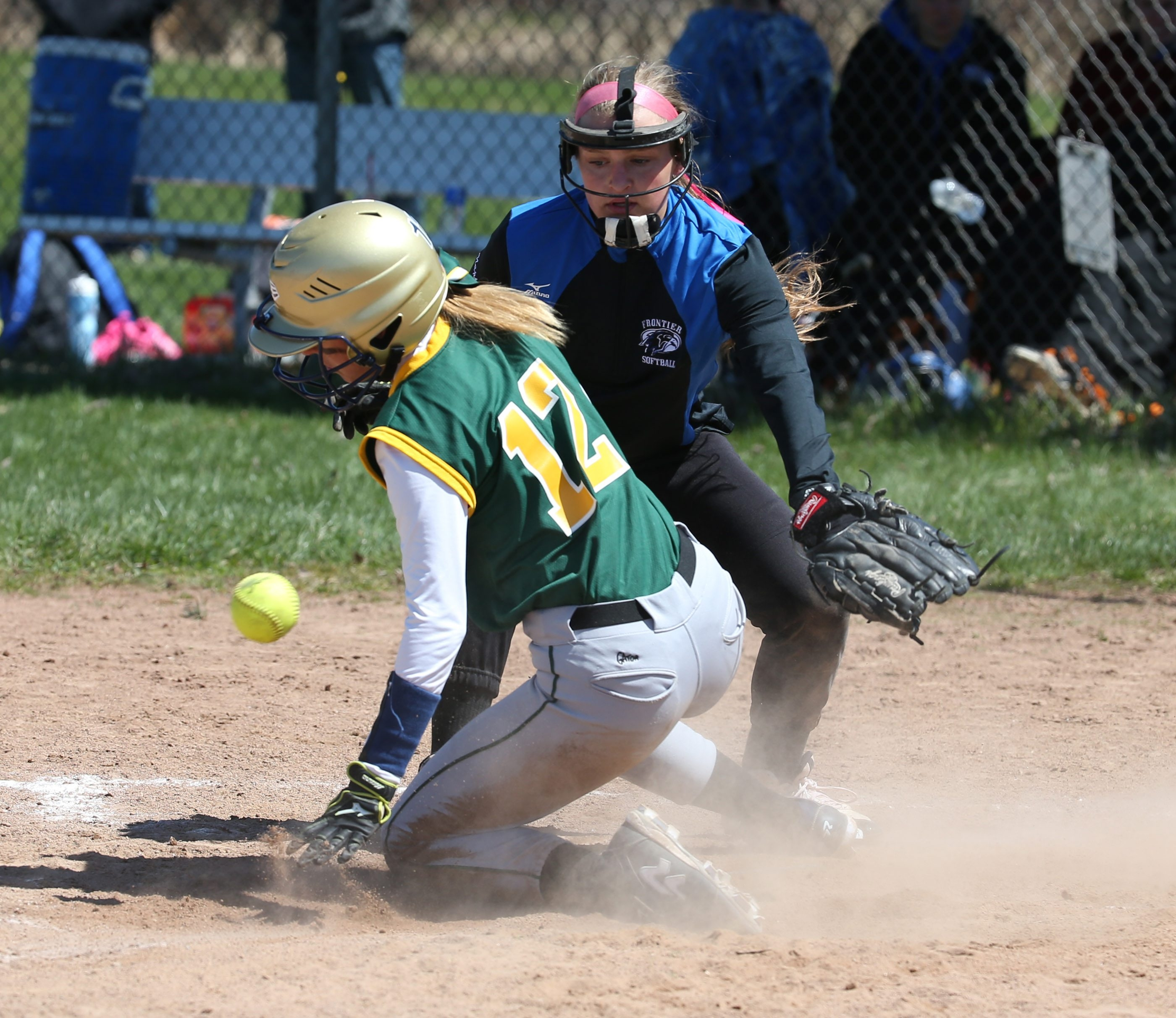 West Seneca East's Brittany Nowatzki slides home safely as Frontier's Oliva Nappo tries to apply the tag in the sixth inning of their game in the Depew Wildcat softball tournament.