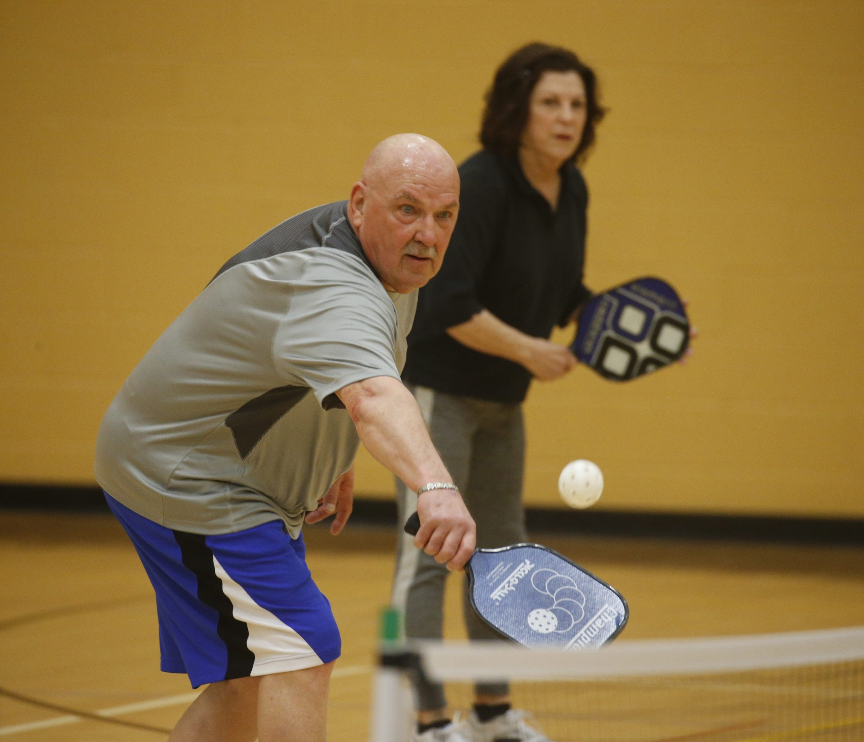 Larry Gross plays pickleball, a newly popular combination of tennis and Ping Pong, at Independent Health Family Branch YMCA.  (John Hickey/Buffalo News)