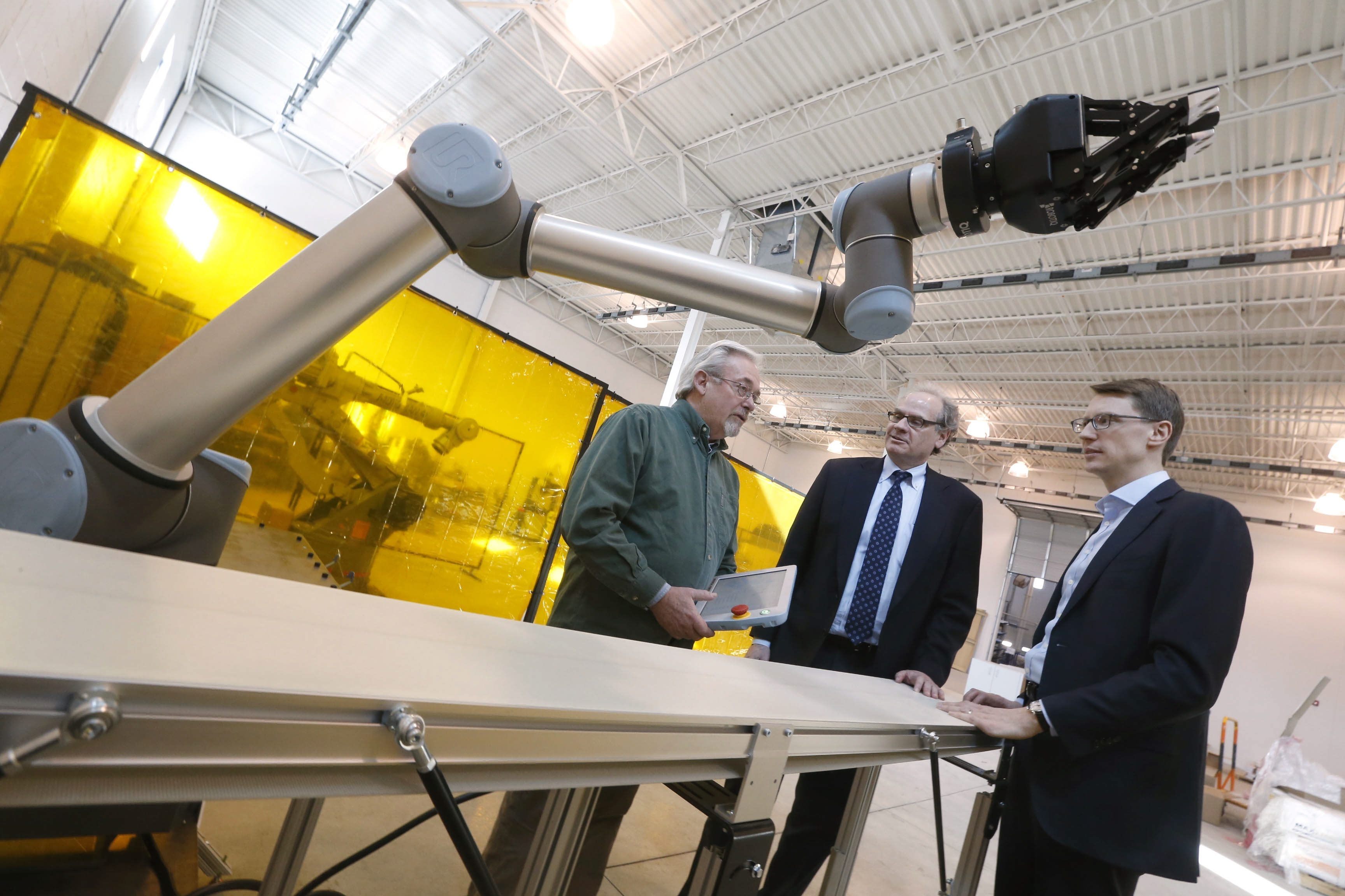Prime movers at Buffalo Manufacturing Works – from left, EWI tech leader Ron Brown, Empire State Development chief Howard Zemsky and Michael Ulbrich, the resource center's president – discuss a new industrial robot.