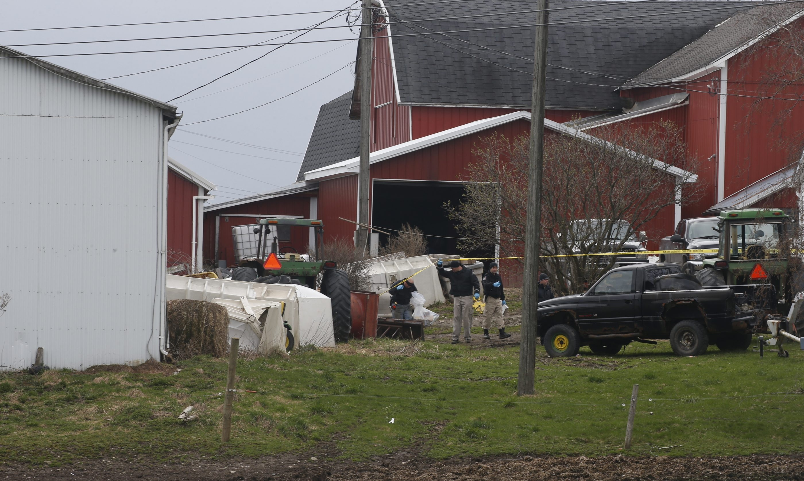 State Police investigators comb through the yard of an Attica dairy farm Tuesday after the body of Douglas Mess was found beneath a manure pile.  (John Hickey/Buffalo News)