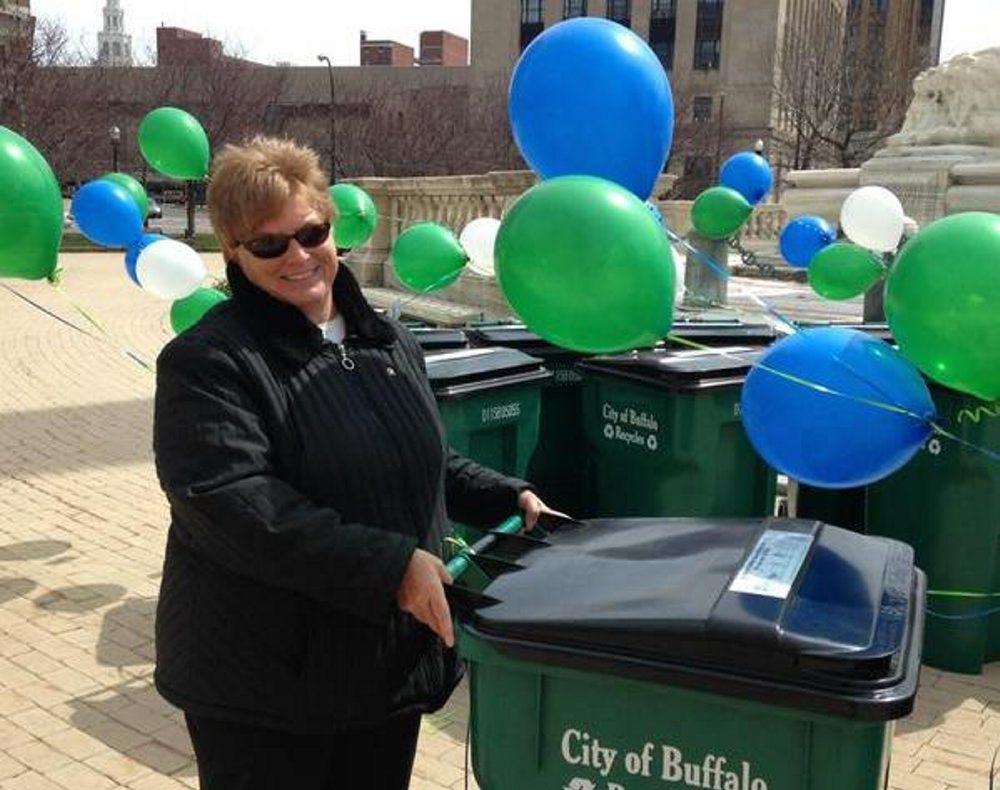 Martha Meagan straightens out balloons and cans as Buffalo gets ready to start a new recycling campaign.