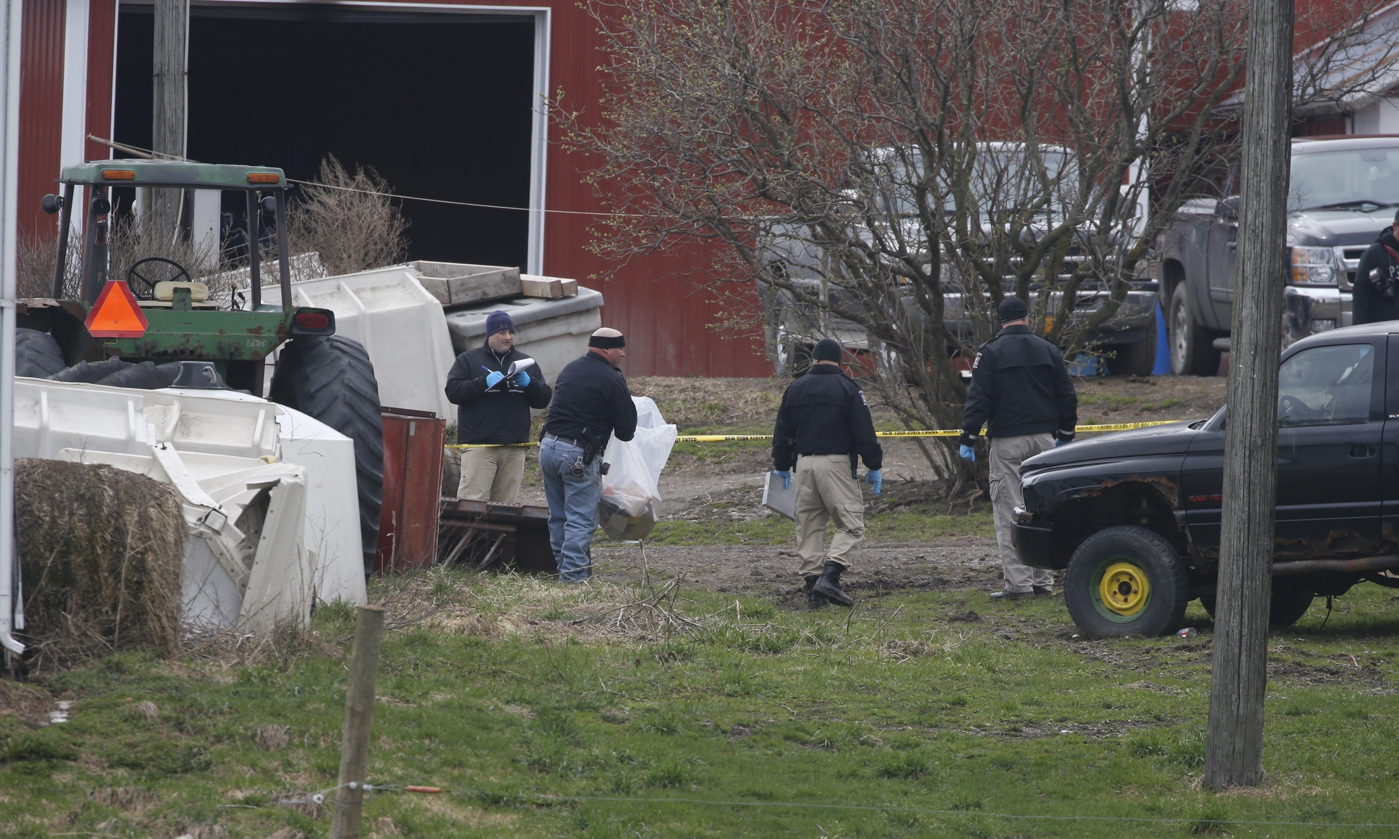State Police investigators comb through the yard after the body of Douglas Mess was found beneath a manure pile at his Attica farm Tuesday. His wife of 30 years, Charlene Mess, has been charged with murder.