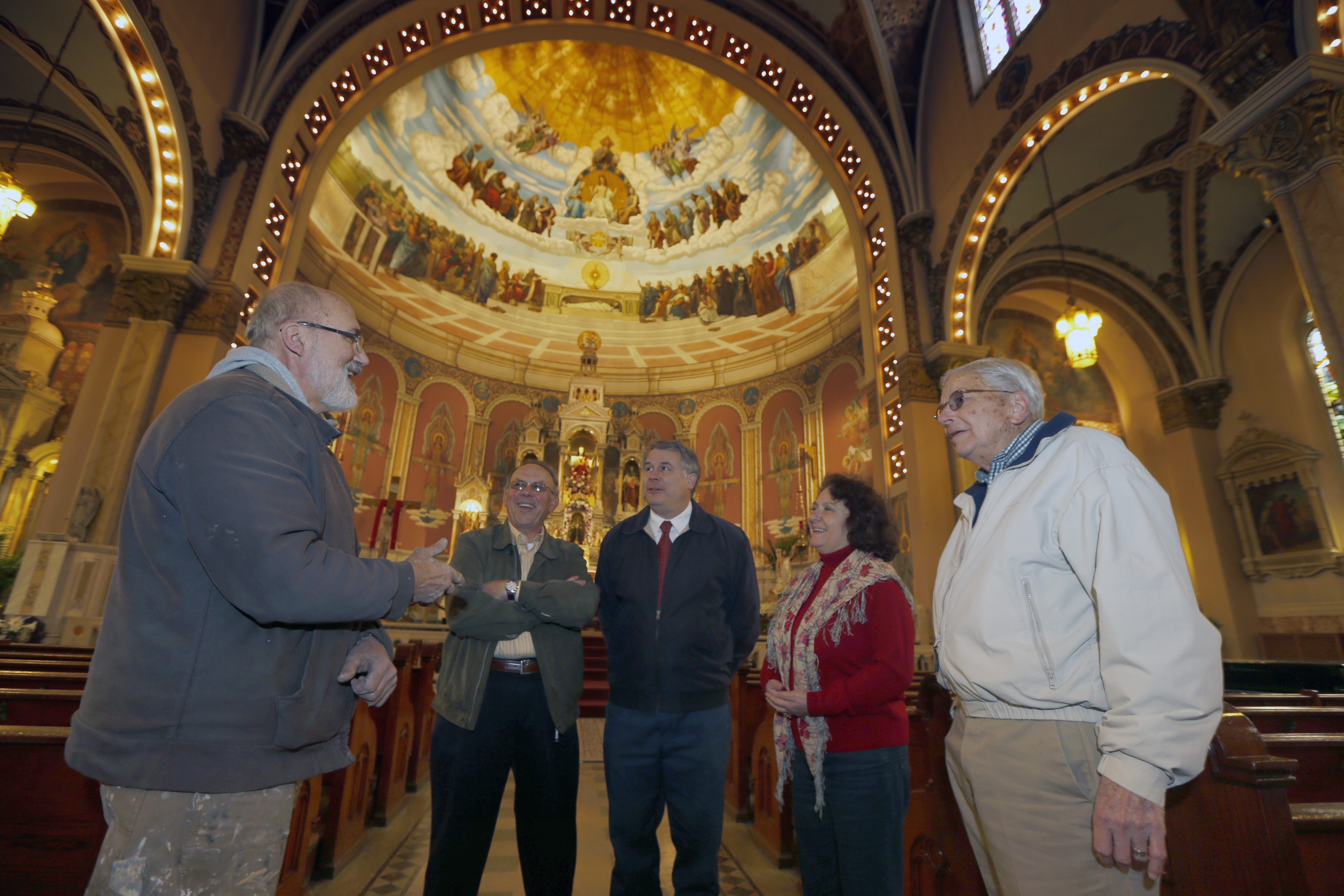 "With ""Disputa"" mural as backdrop, art restorer Henry Swiatek, left, and fellow Friends of Corpus Christi leaders – from second left, Thaddeus Fyda, Martin Ederer and wife and President Lucia Ederer, and William Koch – discuss grass-roots restoration of church."