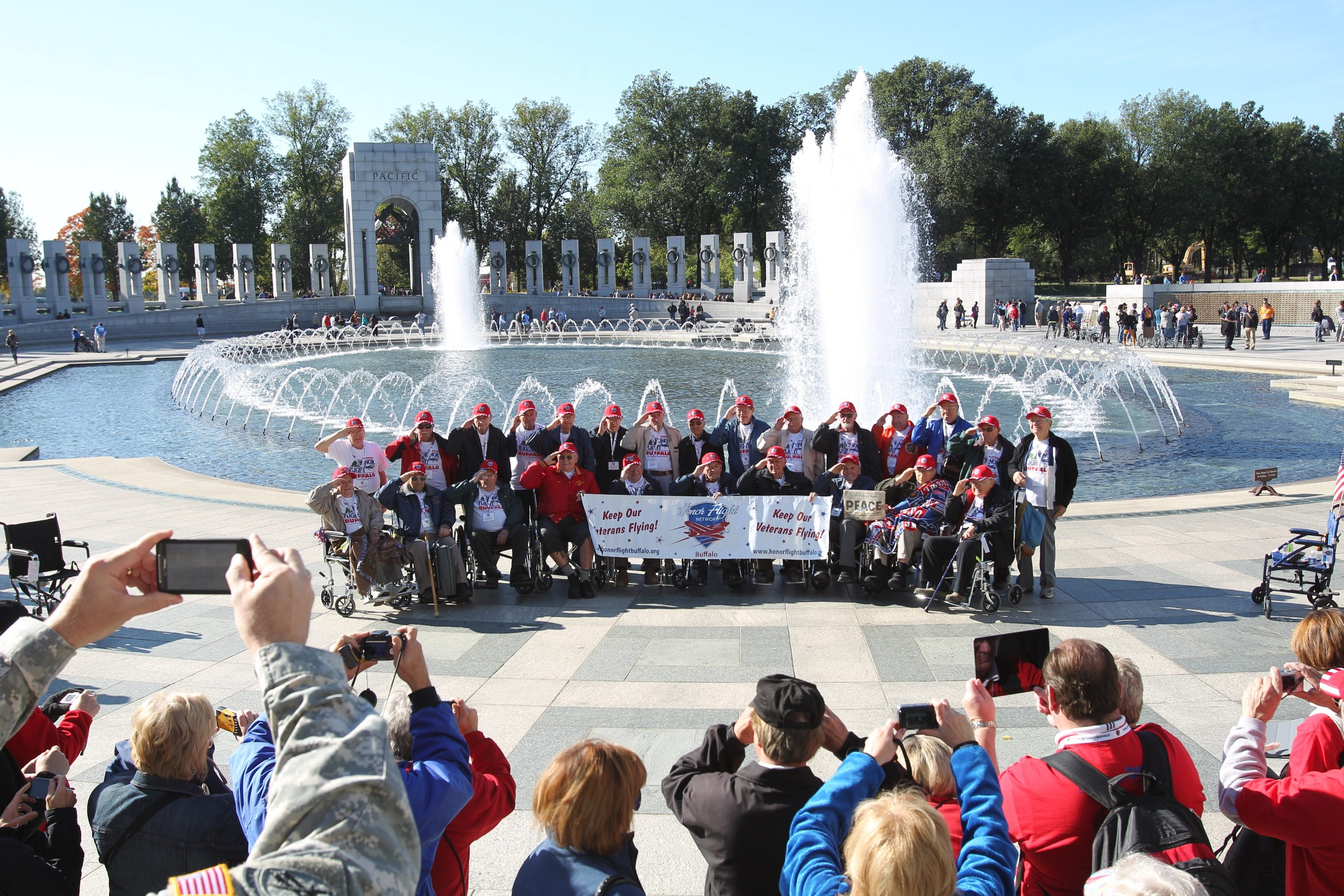 World War II veterans were taken to see the World War II Memorial as well as other memorials on a one-day trip with Honor Flight to Washington D.C., on Oct. 13, 2012. Family and friends accompanying the vets get the group photo at the WWII memorial.