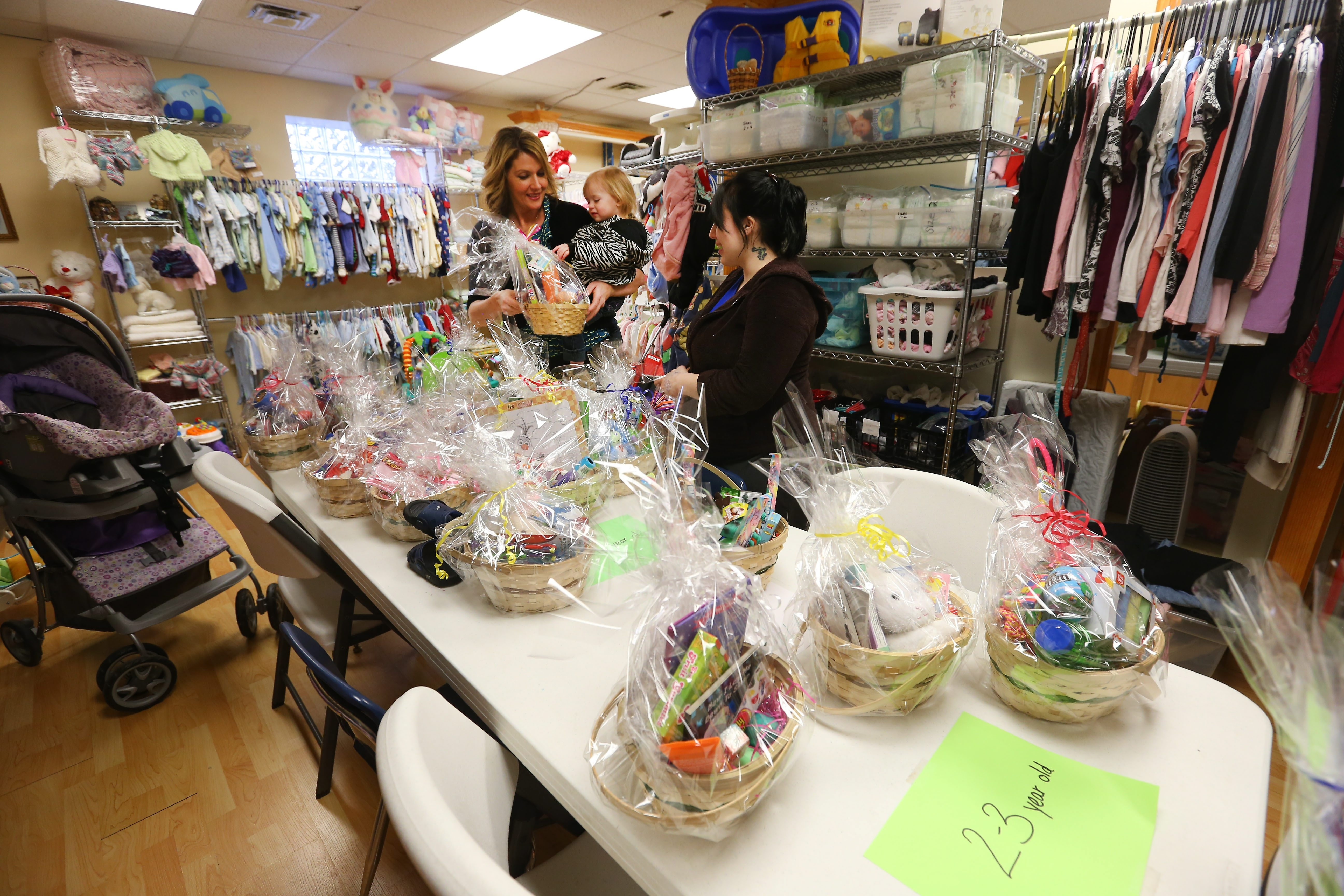 Barbara J. Bidak, executive director of nonprofit Summit Life Outreach Center, 1622 Pine Ave., holds Kylie Clark, 2, while the girl's mother, Destiny Tamborello, one of the center's more than six dozen clients, looks at items in the Parenting Shop.