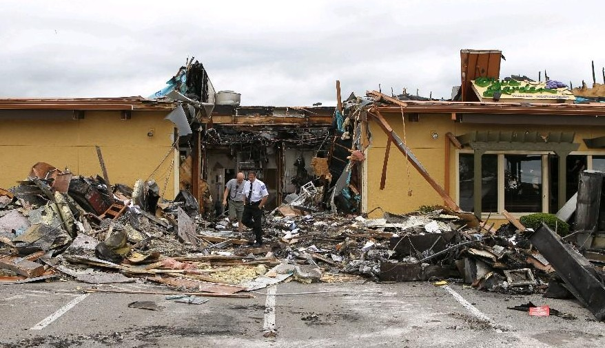 Fire officials tour the rubble after fire at the Olive Garden on June 14, 2014. (James P. McCoy/ Buffalo News)