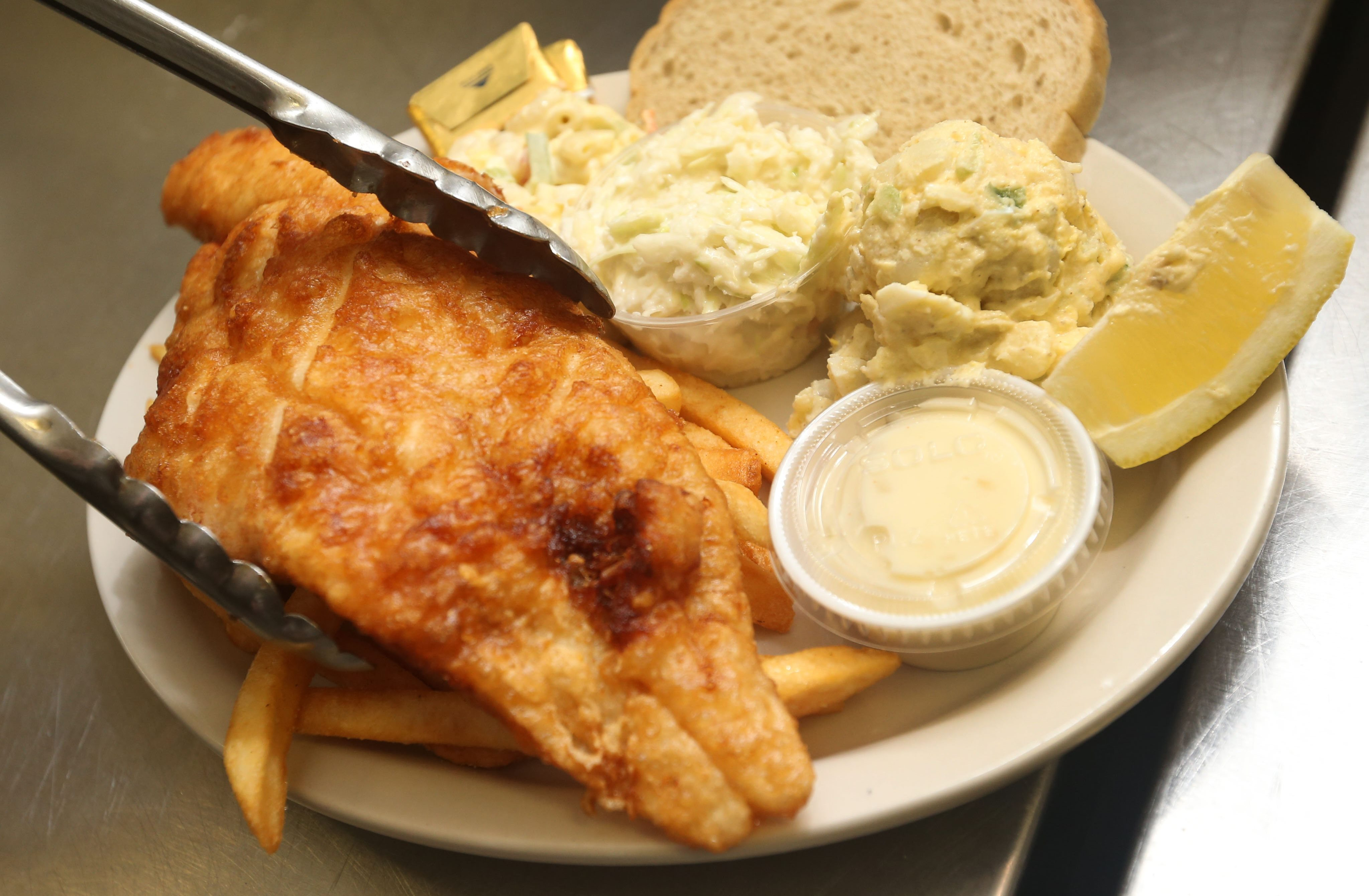 The fish fry at the Buffalo Irish Center in South Buffalo features beer-battered haddock with coleslaw, macaroni salad, potato salad, fries and rye bread. Haddock has not always been the fish of choice, though. (Sharon Cantillon/Buffalo News)