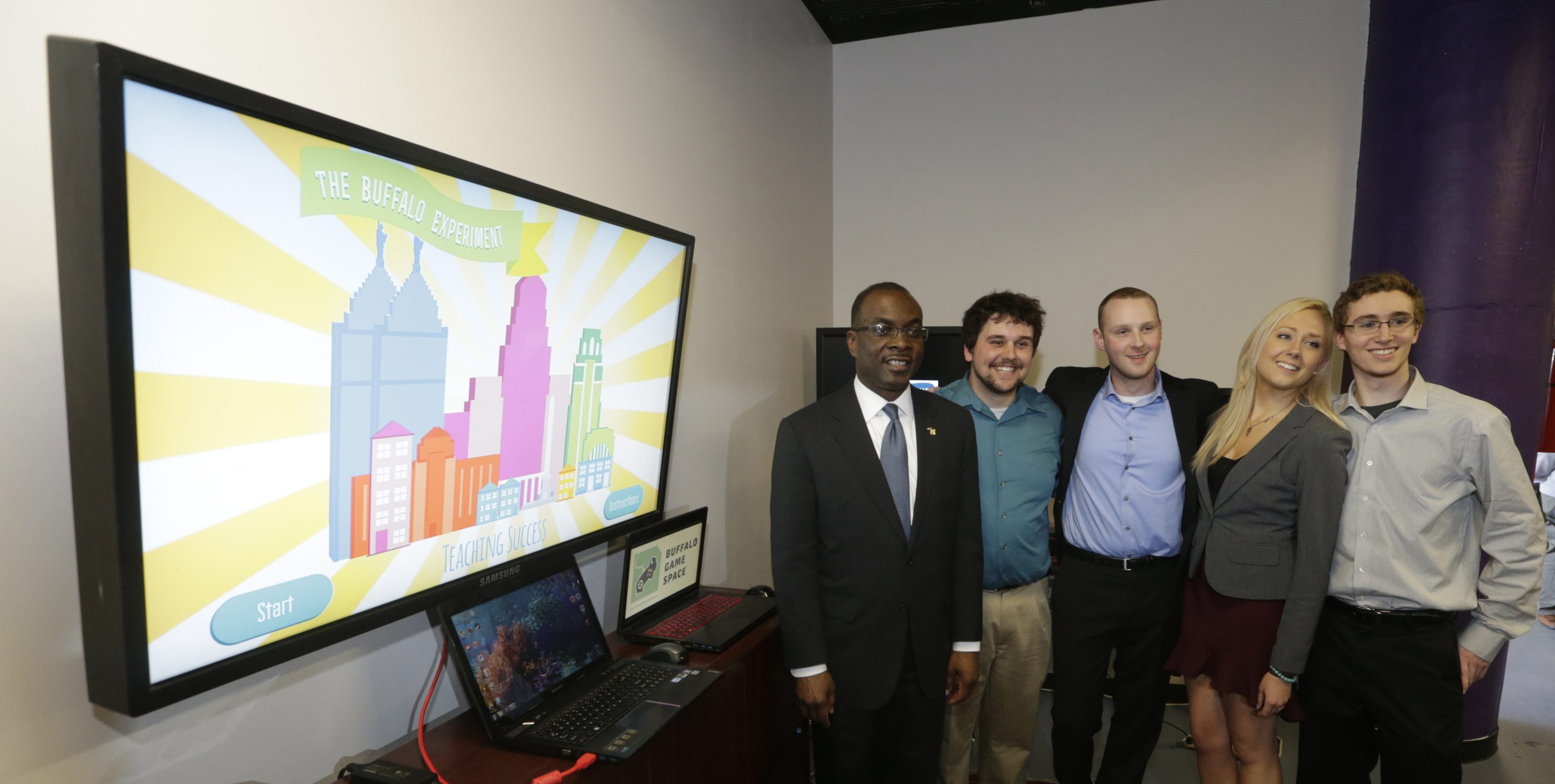From left, Mayor Byron W. Brown poses for a photo with Canisius College students David Kaplan, Pat Kesterson, Brooke Ballard, and Jared Brown, the winners of the city's first serious computer game design competition, on Saturday at the Tri Main Building in Buffalo.