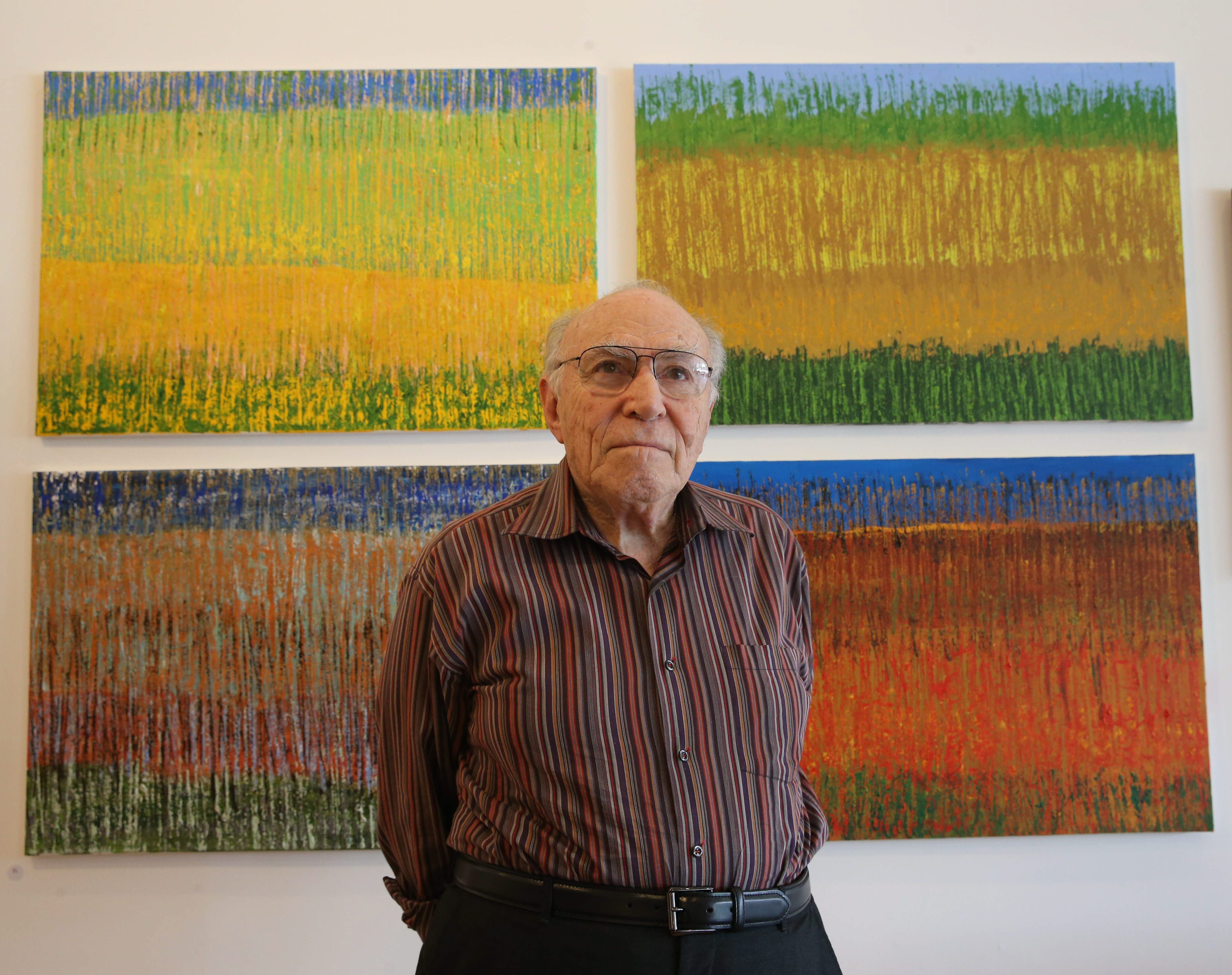 "The paintings and prints of Harold Cohen, dean emeritus of the University at Buffalo's School of Architecture and Planning, are featured in an exhibition at Manuel Barreto Gallery through June 26. Behind him is his painting ""The Four Seasons."""