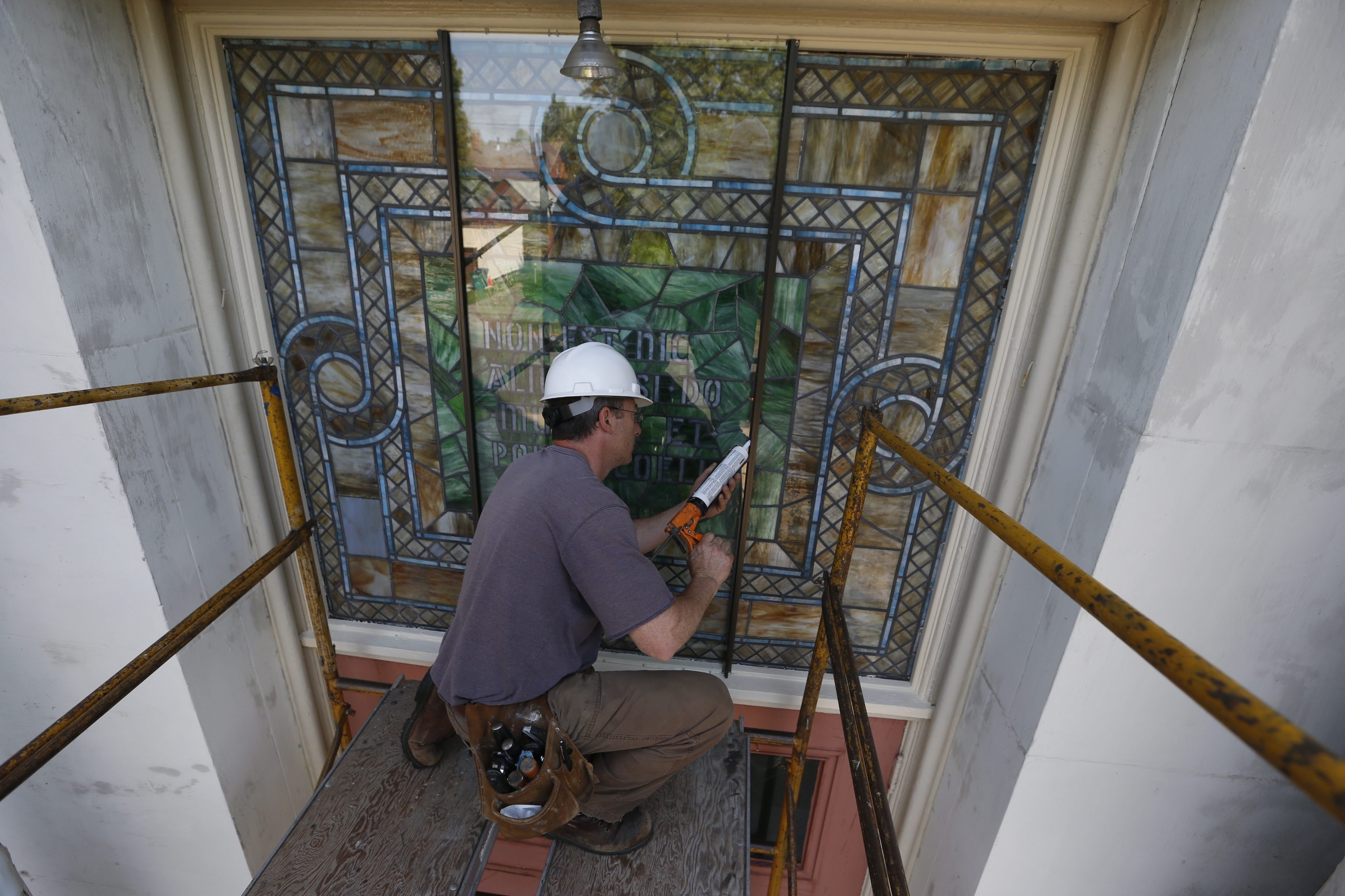 Colin Albig from Images in Glass installs a sheet of glass that will clearly reveal but also protect one of the three stained-glass windows discovered hidden behind Plexiglas at the Religious Arts Center in Black Rock. The building was formerly St. Francis Xavier Church.