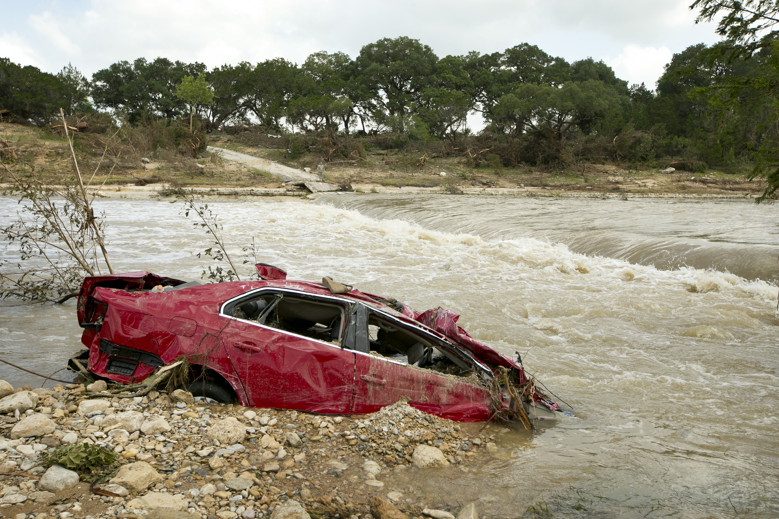 A destroyed car is submerged in the Blanco River in Wimberley, Texas, after Tuesday's flooding.