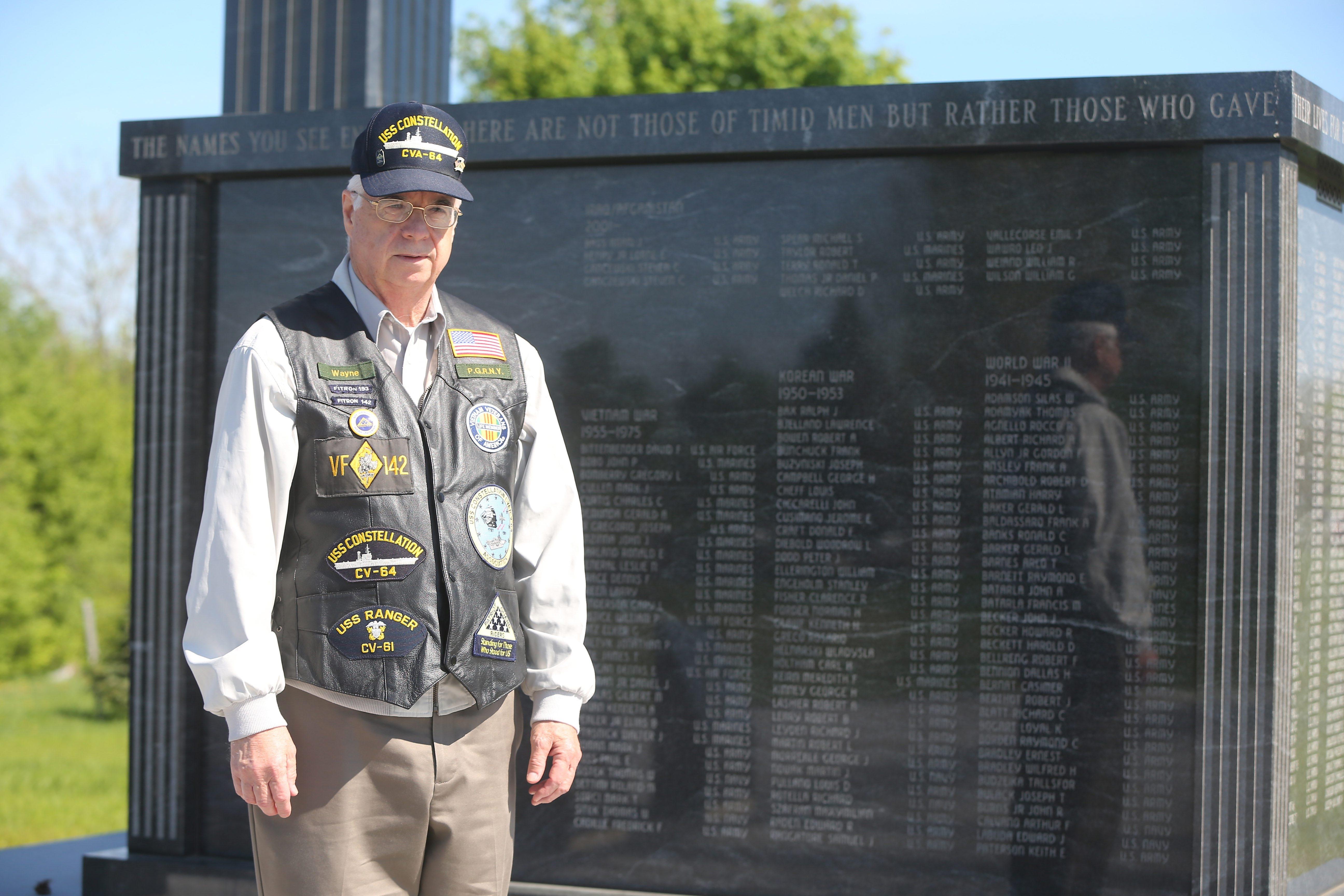 At Niagara Falls Veterans Memorial in Hyde Park, Wayne Bridgeman honors memory of Gary Henderson, Gilbert Nicklas and Thomas Sitek.