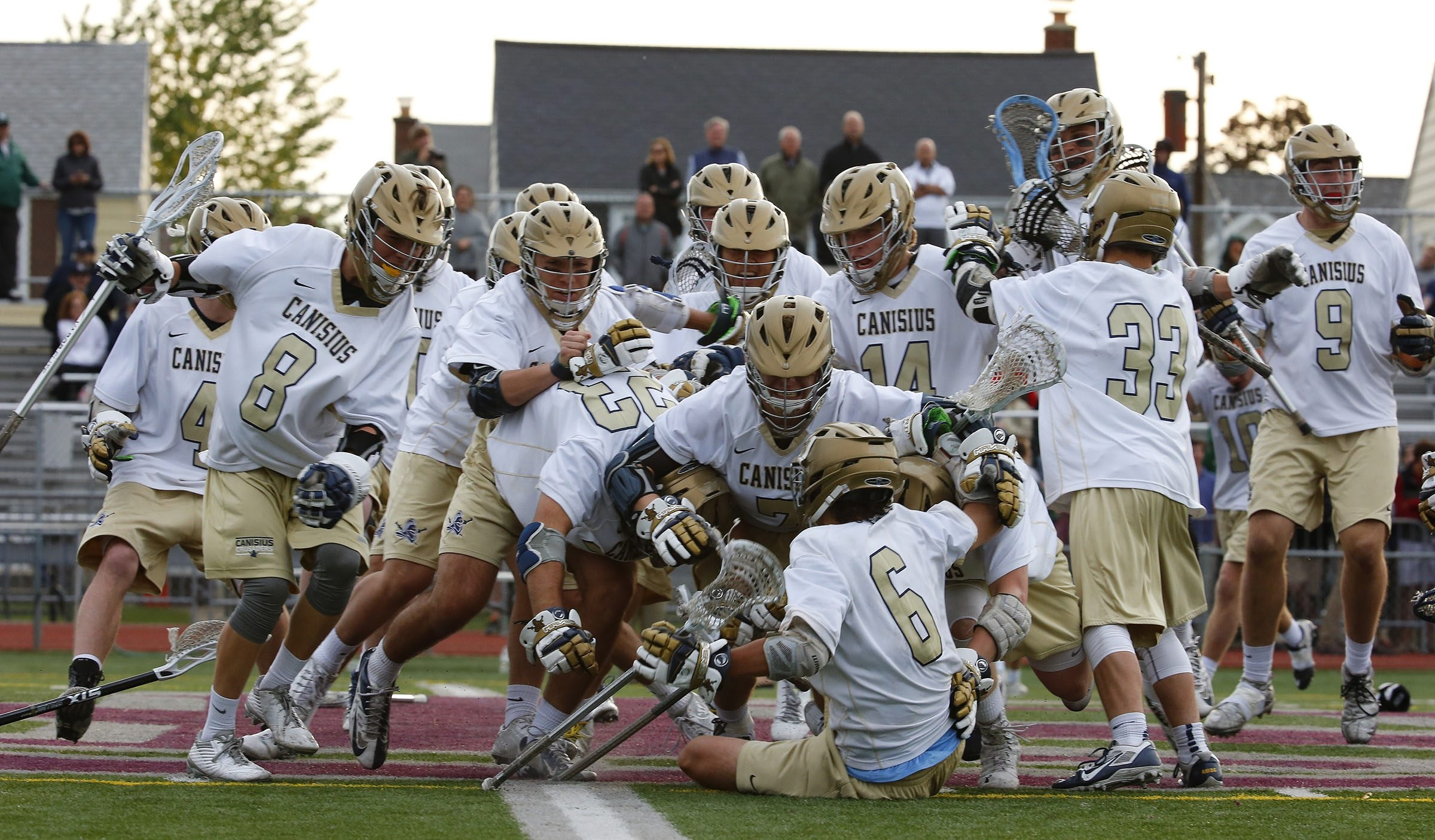 Canisius players mob Reid Martin (6) after he scored the winning goal in the fourth overtime to beat Nichols, 7-6.