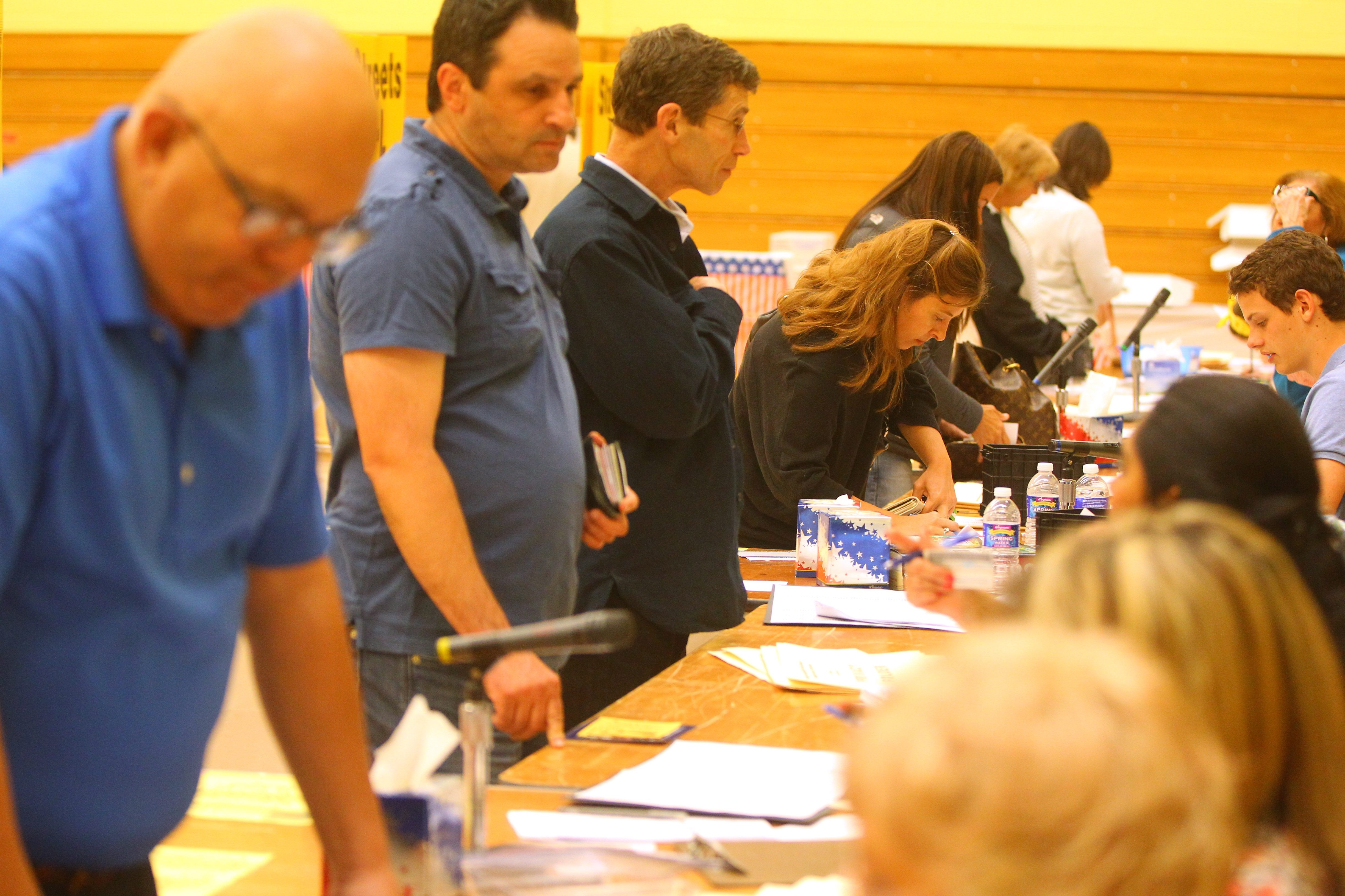 Voters in the Williamsville School District passed the budget and spending propositions handily, while ousting two board members. Here, residents sign in to vote in the gym at Williamsville North High School. (Mark Mulville/Buffalo News)