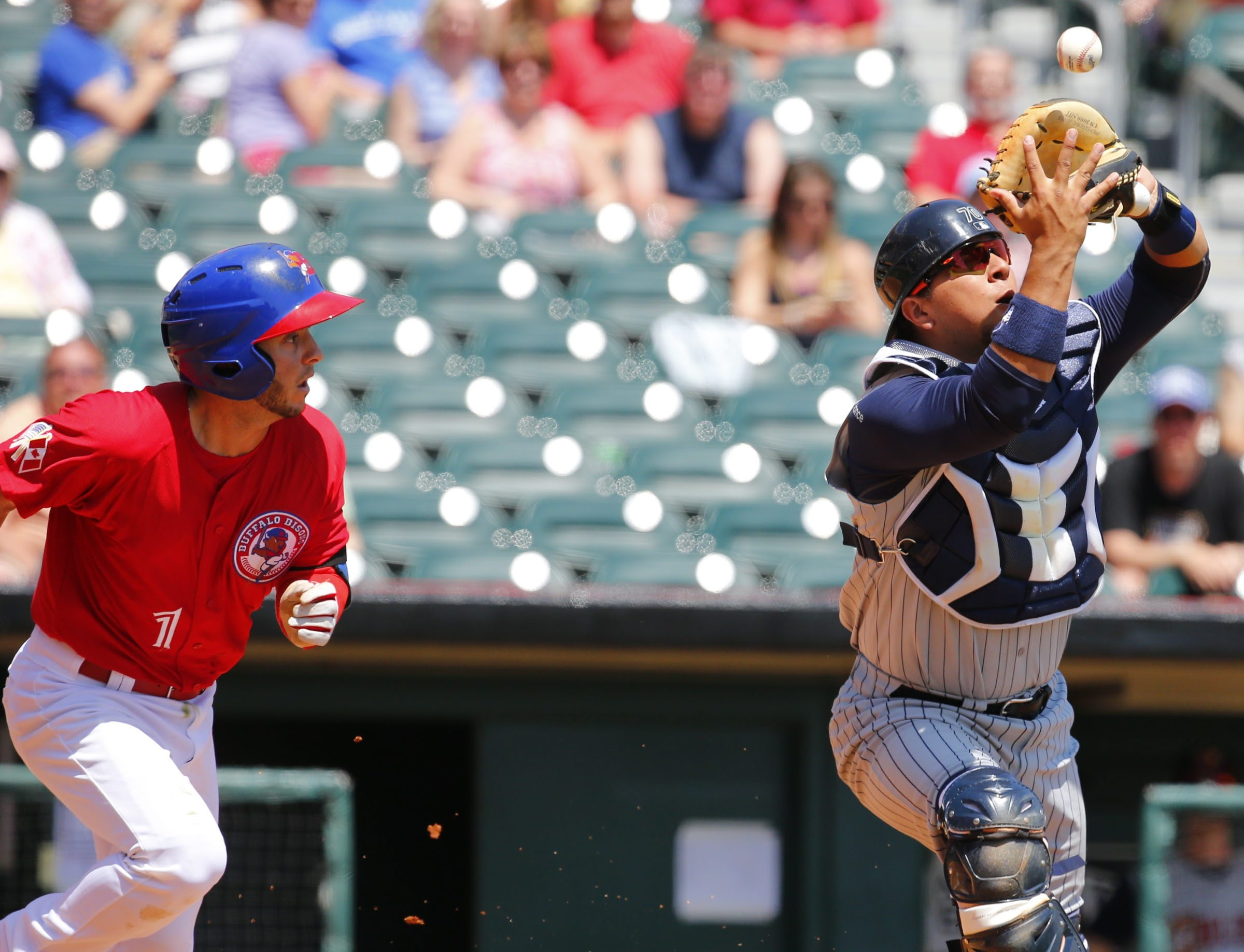 The Bisons' Jonathan Diaz pops out to Toledo Mud Hens catcher Miguel Gonzalez attempting to bunt in the third inning at Coca-Cola Field on Sunday.