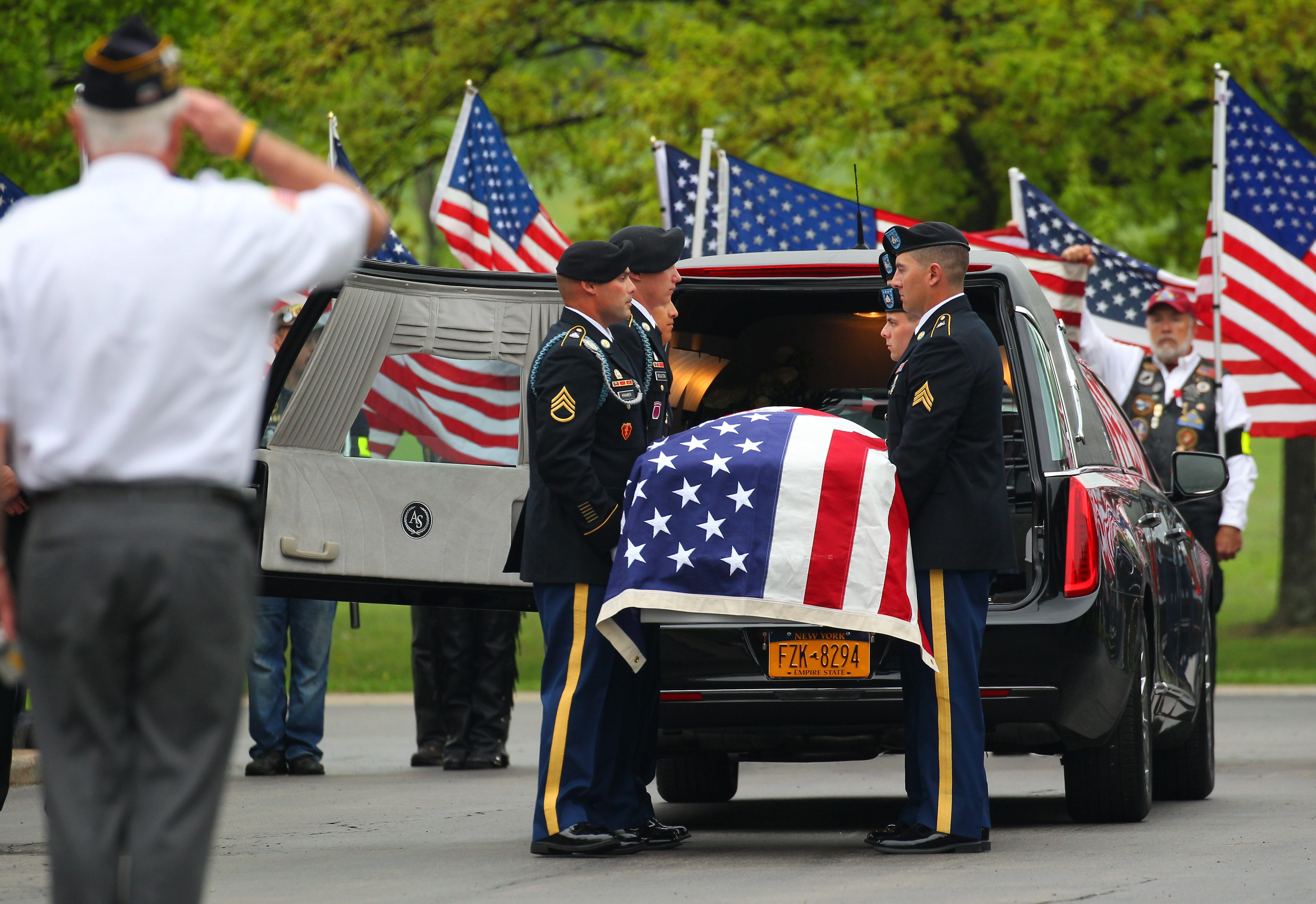 Servicemen remove the flag-draped casket of Capt. John J. Levulis from the hearse at Eden High School on Saturday.
