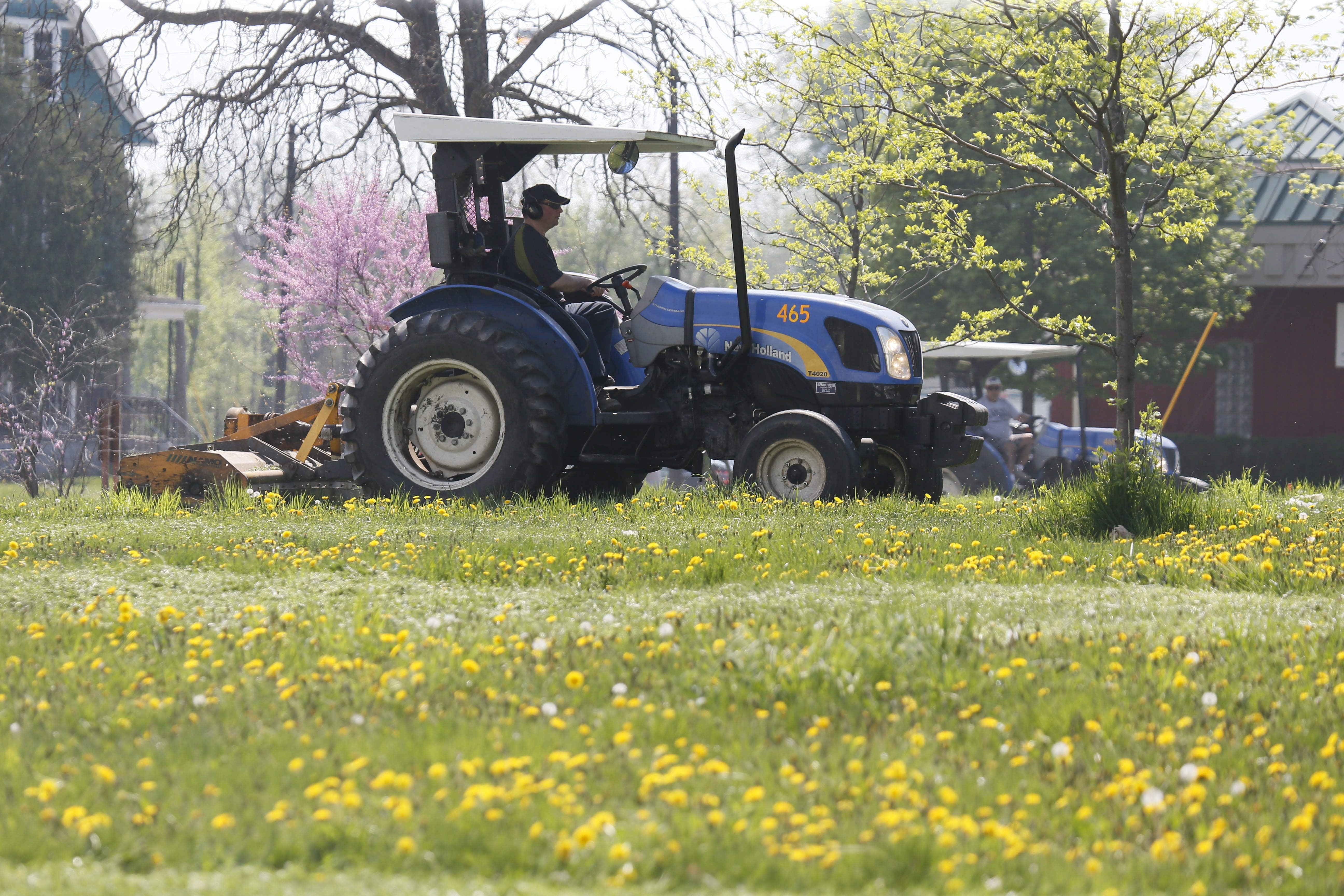 A city crew mows a vacant lot on Genesee Street between Strauss and Wilson streets on Monday.