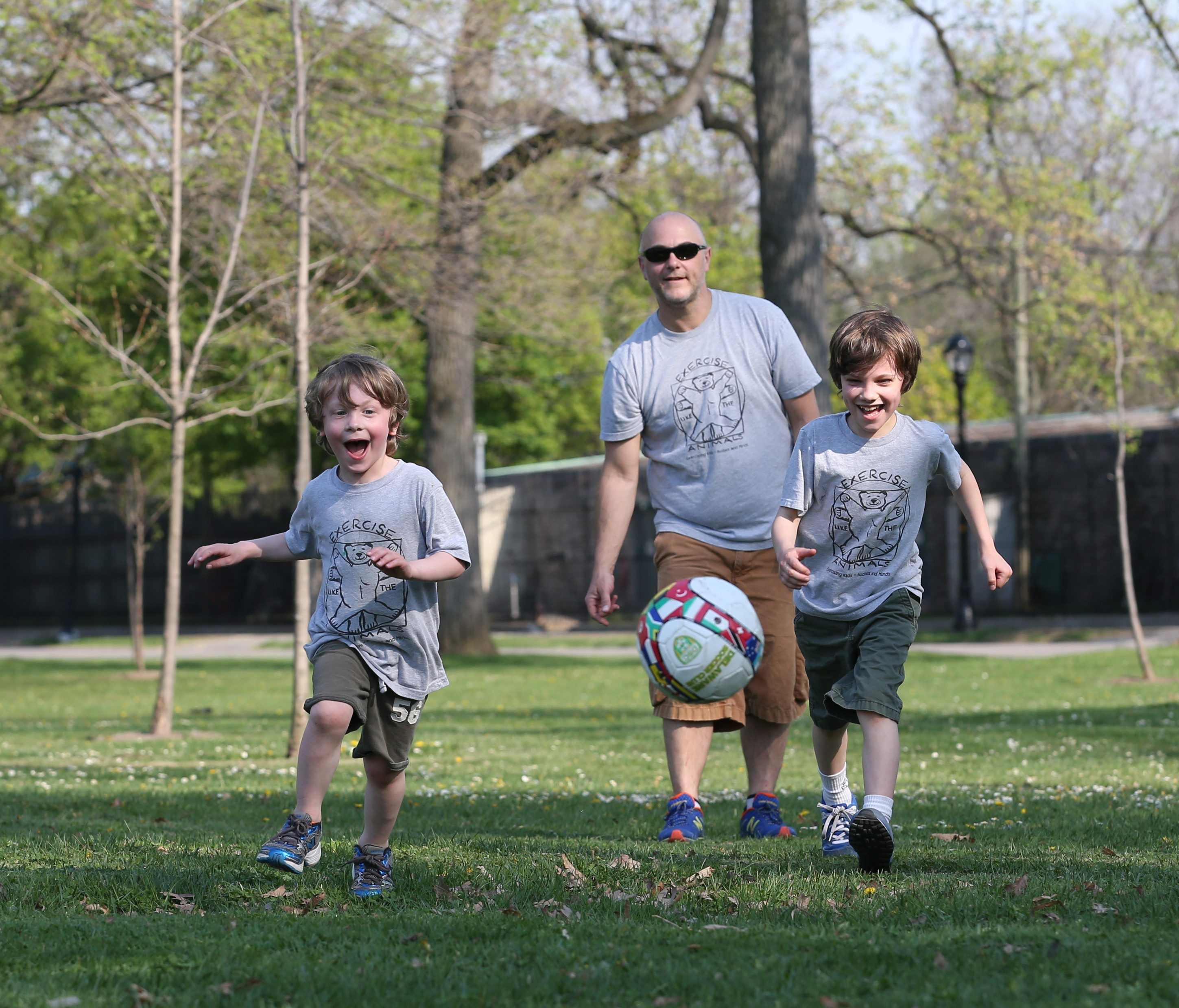 Jerry Turcotte and his wife Diana Proske walked to Delaware Park to play with their sons Simon, 4, left, and Max, 8, Friday, May 8, 2015.  (Sharon Cantillon/Buffalo News)