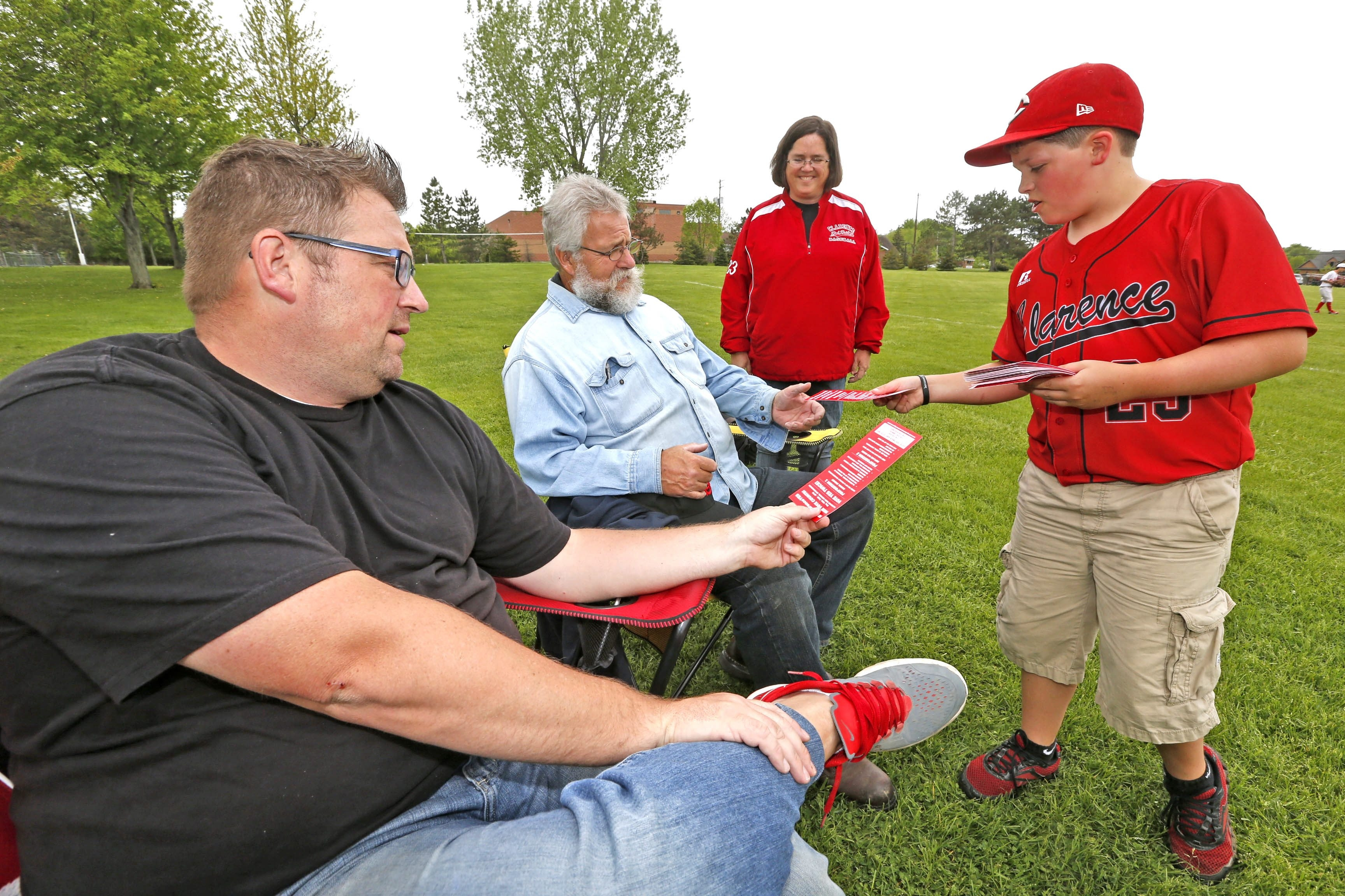 Sean Andrews, 12, with his mom, Tricia, observing in back, passes a pamphlet about Tuesday's school vote to Clarence residents Adam Corry, left, and his dad, Dave Corry, who were watching a baseball game at Town Place Park in the town on Friday.