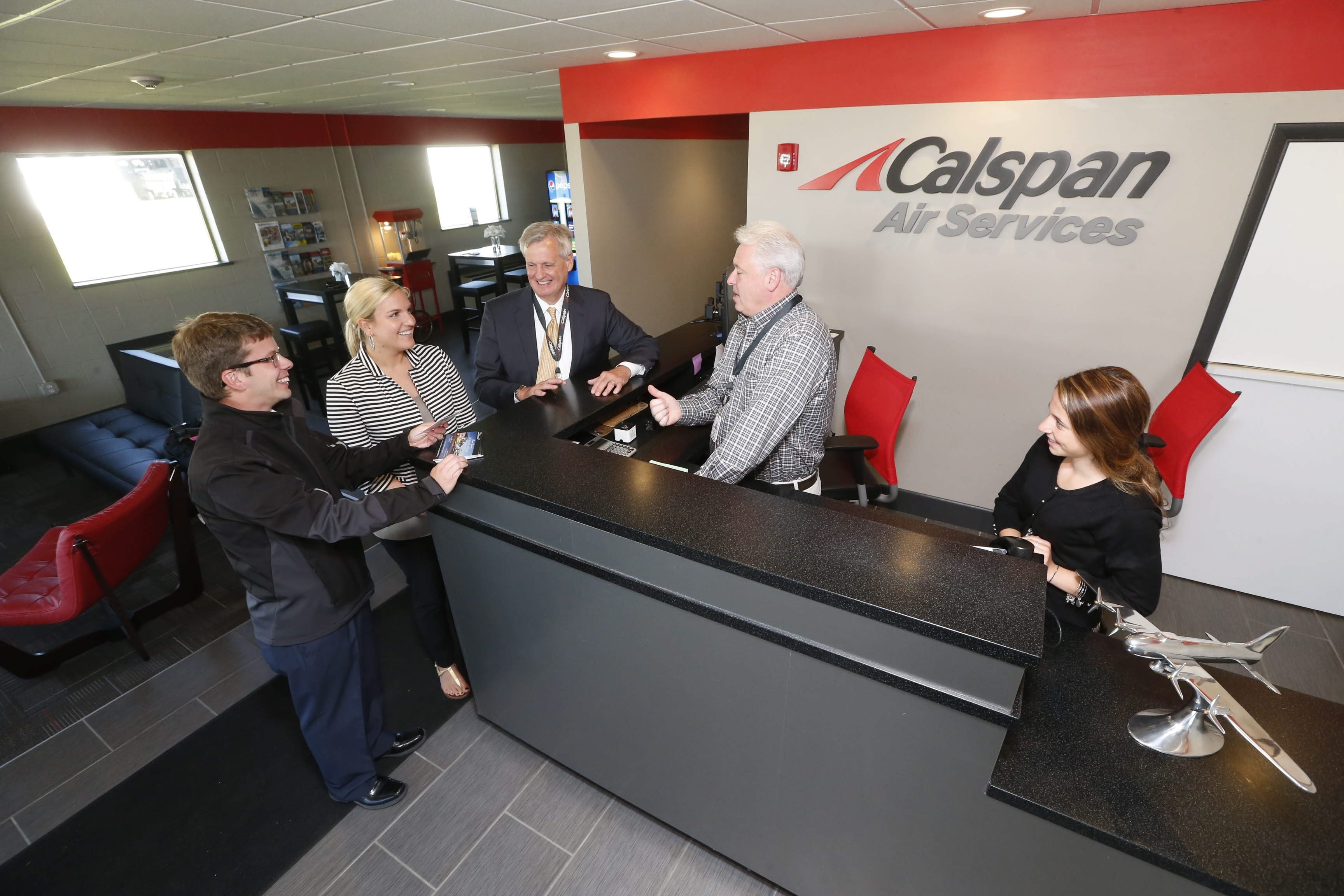 Getting ready for the Calspan Air Services open house celebration on Thursday are from left, Jerry Goupil Jr., director of marketing; employee Kara Devine; CEO Lou Knotts; Jim Celeste, director of fixed-based operations; and employee Barrett Armstrong in the refurbished facility next to Niagara Falls International Airport.