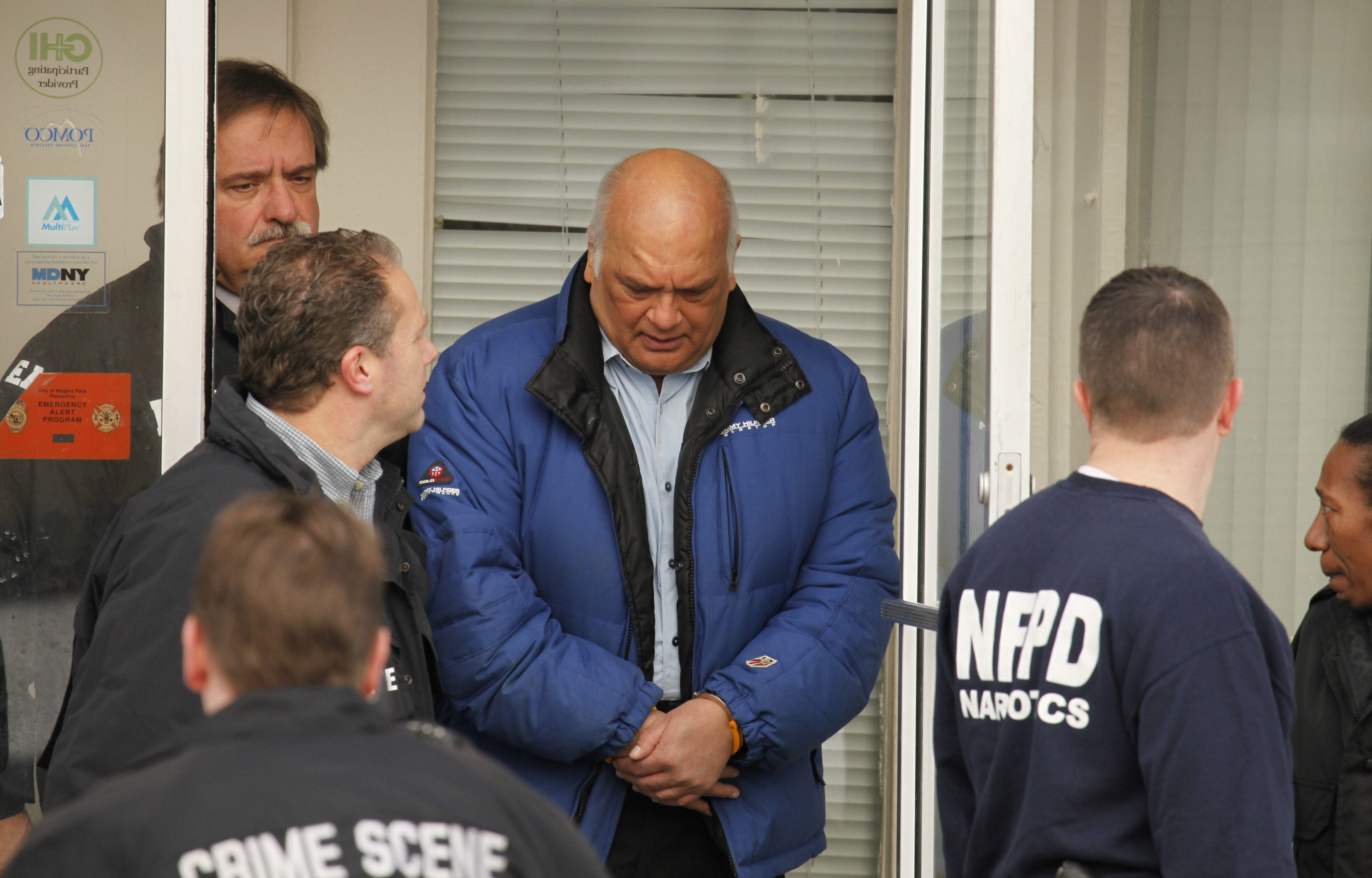 Police lead Pravin V. Mehta, M.D. out of his Niagara Falls in handcuffs early Thursday morning, Jan. 27, 2011.   {Photo by Derek Gee / Buffalo News}