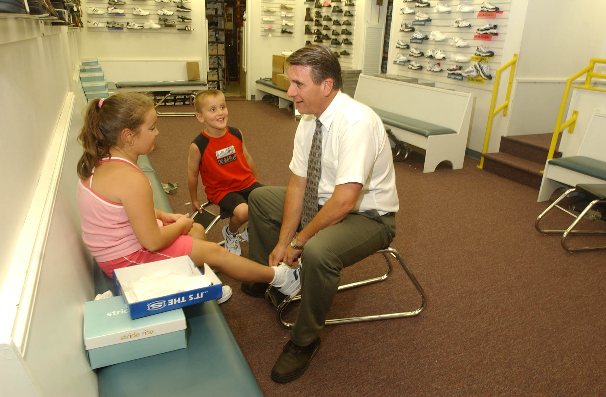Boulevard Mall Bootery co-owner Mark Slayton helps customers Alexa and Tyler Eldridge at the shop in August, 2013. The longstanding children's shoe store announced that it is closing. (Buffalo News file photo)