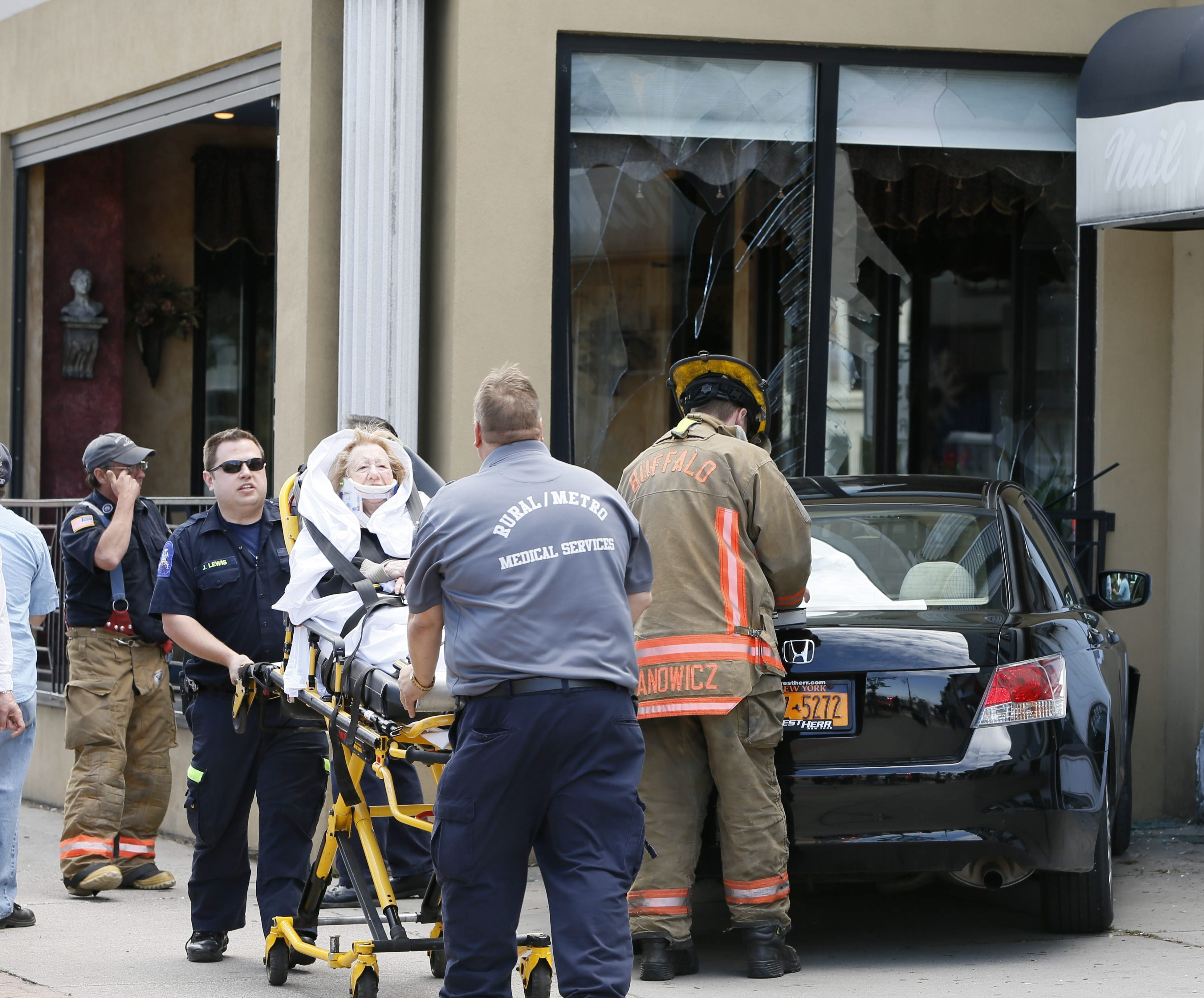 A 90-year-old woman is removed from car she was driving after it crashed into the Kostas Family Restaurant patio on Hertel Avenue. She was taken to the hospital for treatment of minor injuries.