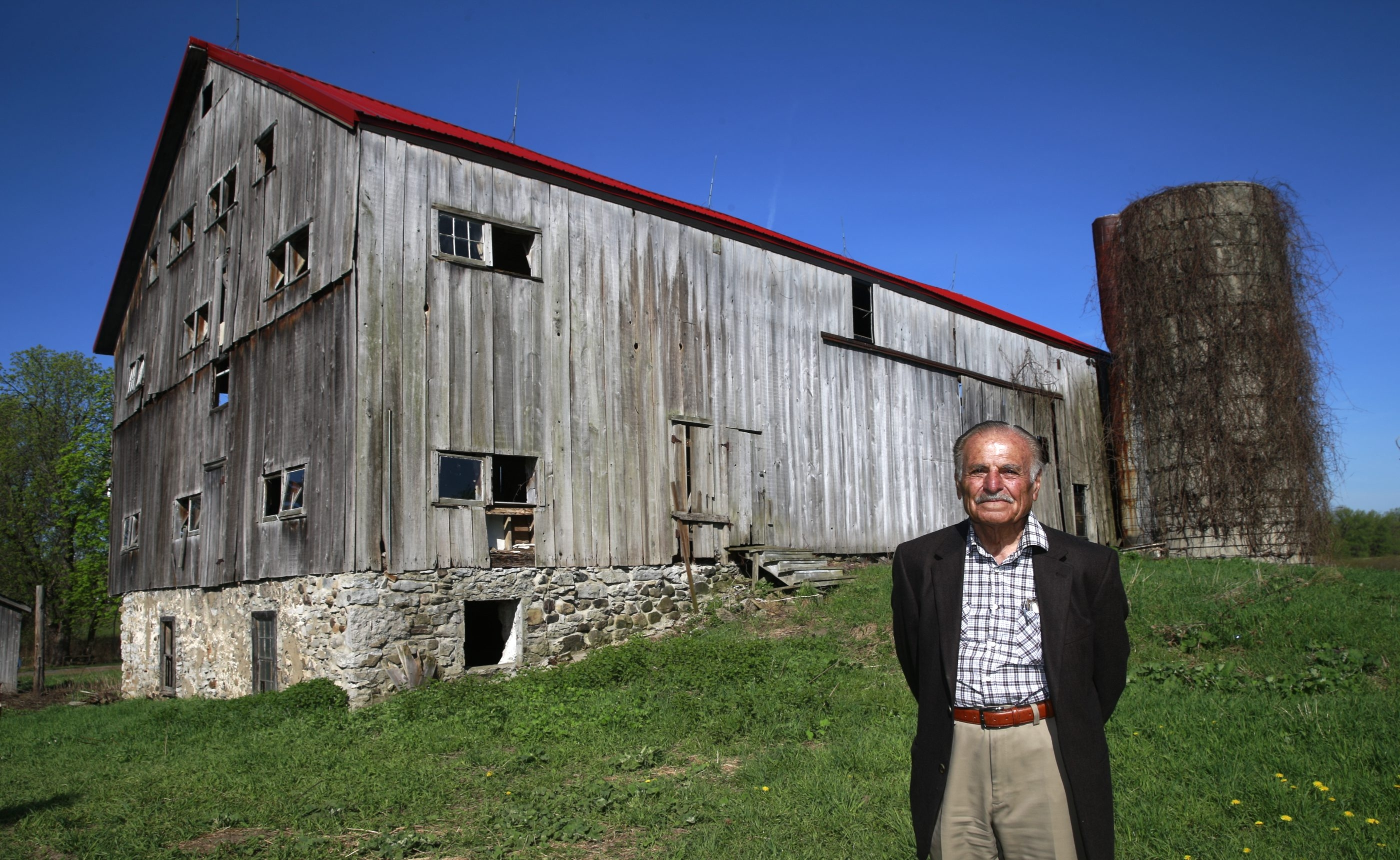 Dr. Ismet Hallac stands before his 19th-century barn, a relic from German Mennonite settlers in Clarence, last week. The surrounding land will become a housing development. Hallac wants to sell the barn to preservationists. See a photo gallery at BuffaloNews.com.
