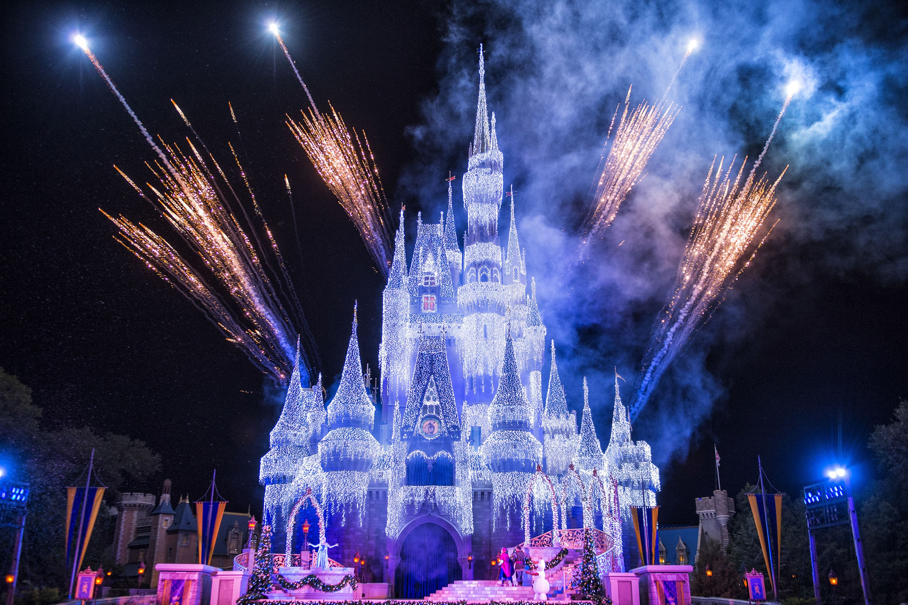 """New in 2014, Queen Elsa from """"Frozen"""" uses her incredible powers to transform Cinderella Castle into a glistening ice palace for the holidays. Joined on the Forecourt stage by Princess Anna, rugged mountain man Kristoff and Olaf, the summer-loving snowman, Elsa bestows this gift onto the people of Magic Kingdom with colorful snowflakes, fireworks and a special effects spectacle bathing the castle in 200,000 shimmering white lights. Magic Kingdom guests are treated nightly to the dramatic """"A Frozen Holiday Wish"""" stage show. (Matt Stroshane/Disney/TNS)"""