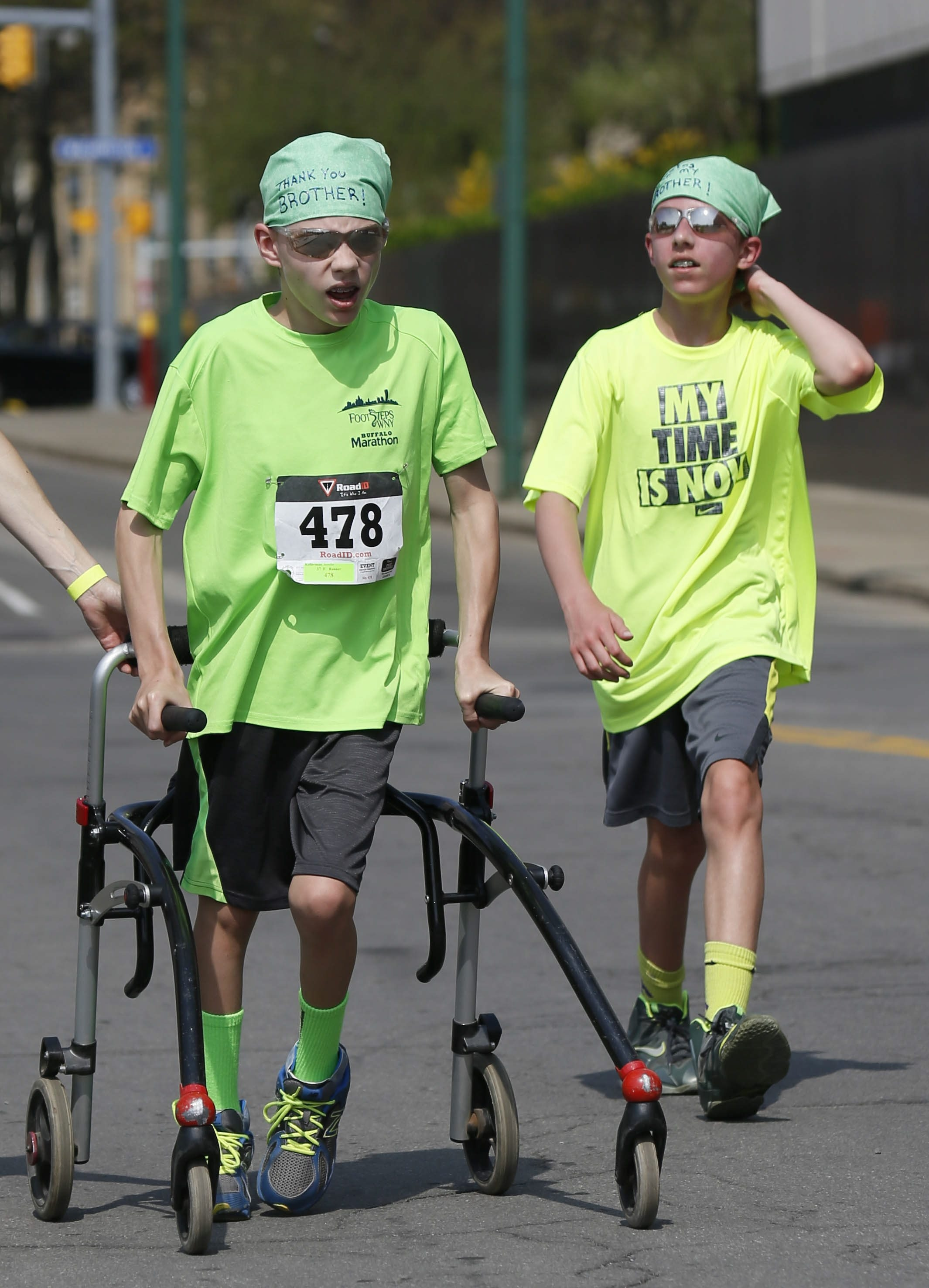 Twins Cody, left, and Justin Cwiklinski, 12, approach the finish line of the Heritage Centers Foundation 5K Walk, Run, Roll on May 9.