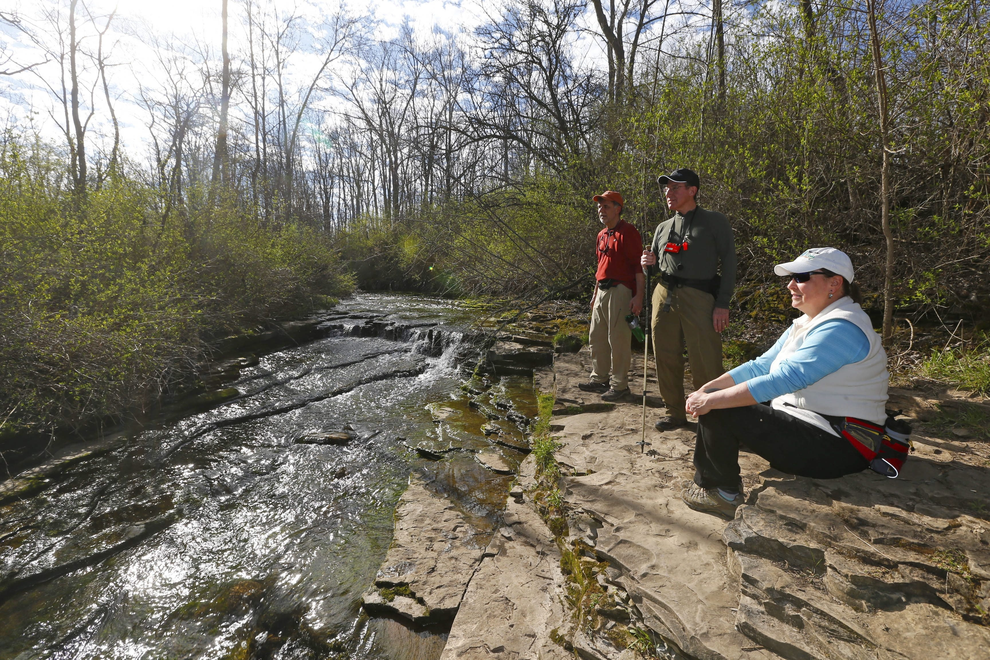 Janet and David Kowalski flank Richard Schraven during a stop along the trail at Royalton Ravine Park in Gasport. The three are members of two local outdoor groups that organize hiking tours.