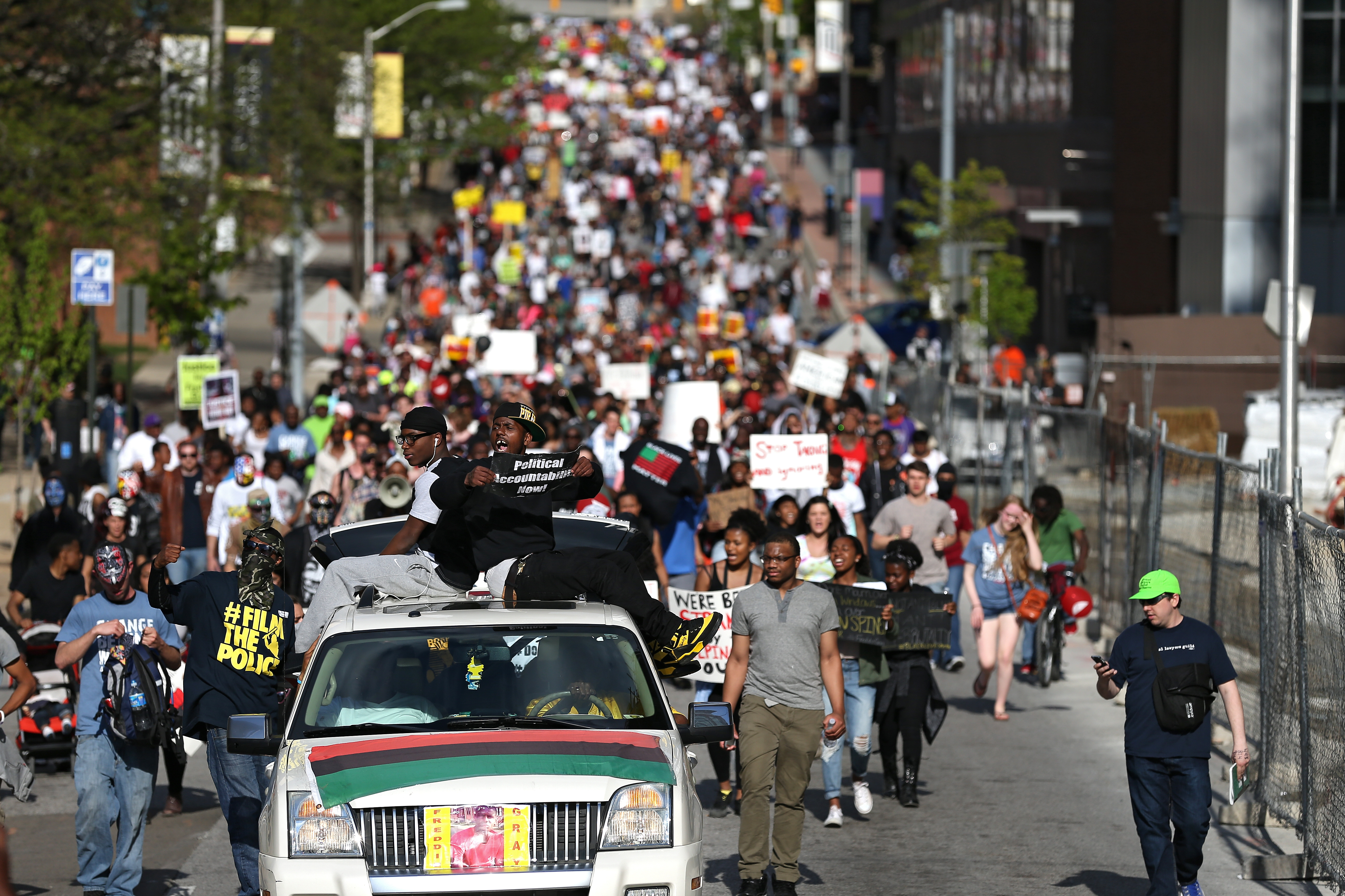 Protesters in Baltimore march on the street from City Hall on Saturday, a day after Baltimore authorities released a report on the death of Freddie Gray.